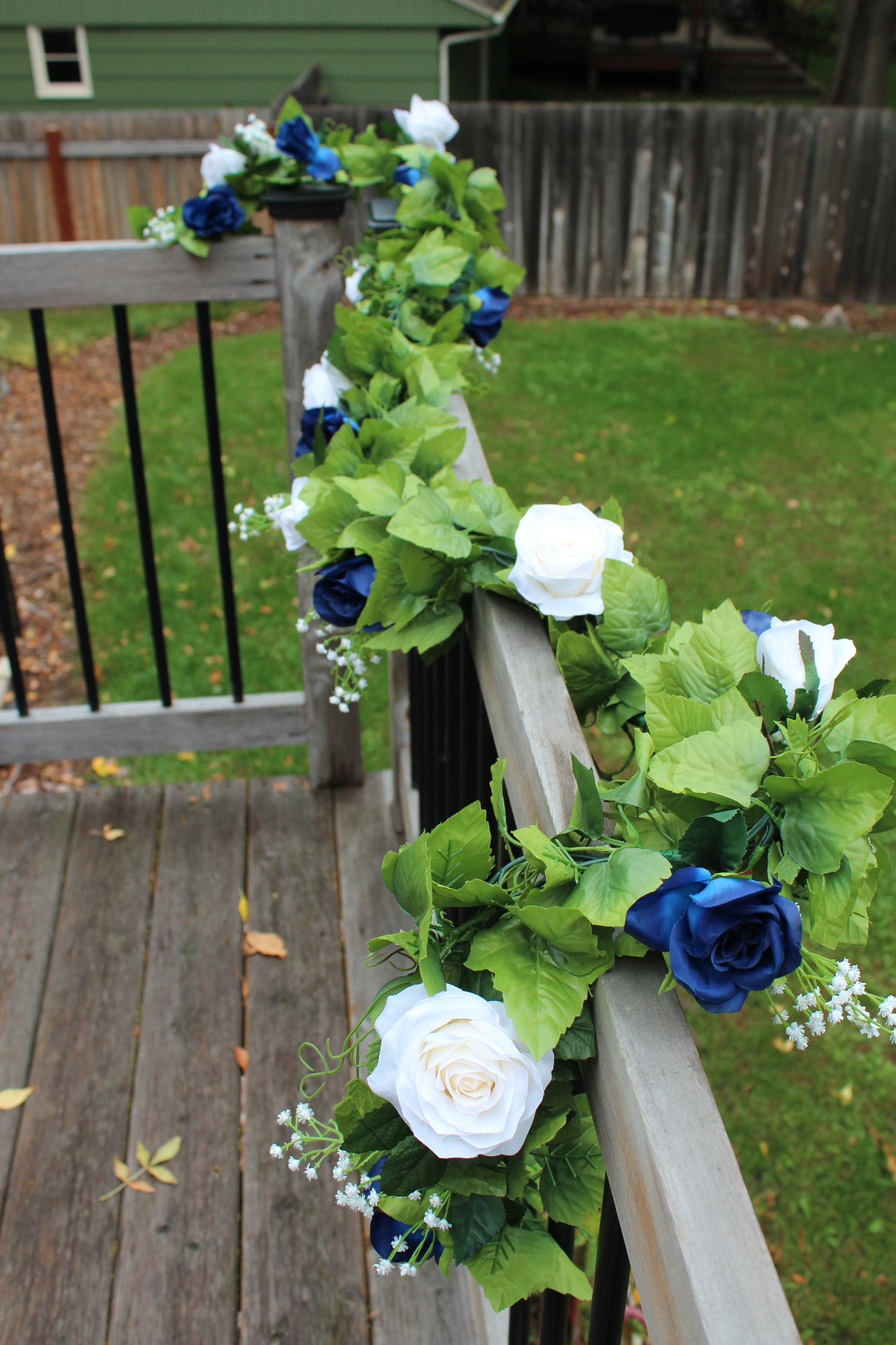 8 foot garland for the head table: blue roses, ivory roses, baby's breath, ivy.