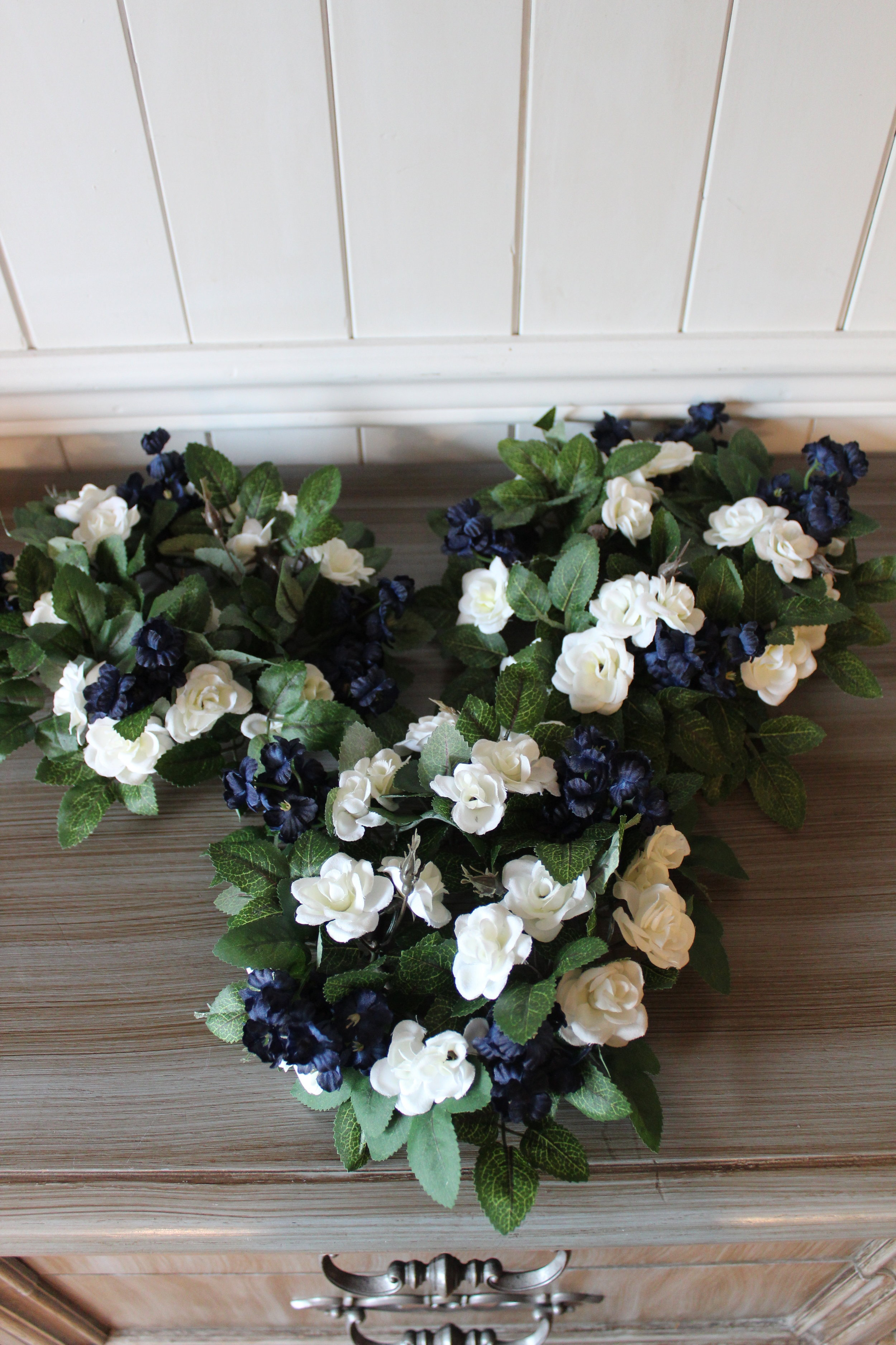 Candle rings for the Unity Candle: ivy, blue accent flowers, mini ivory roses.