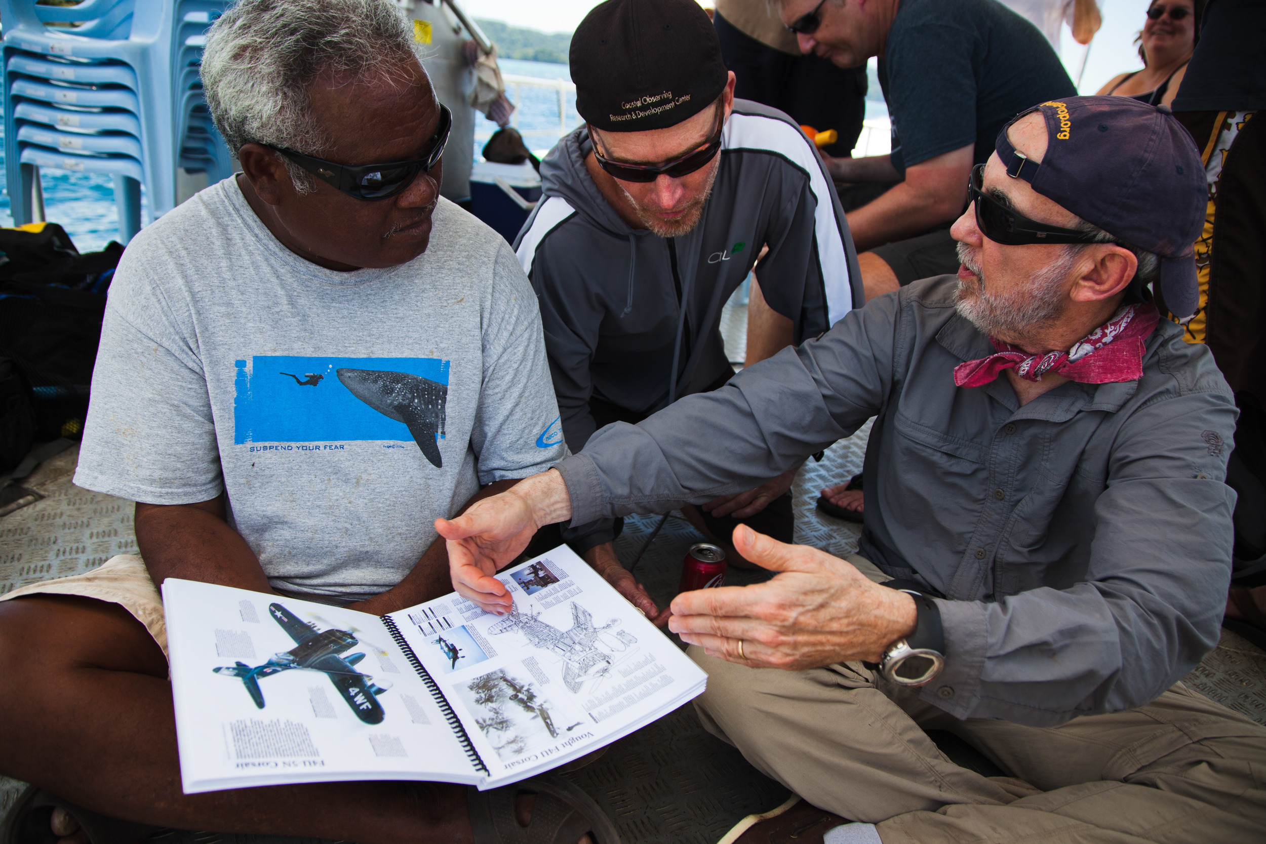 Joe Maldangesang [left] and Pat Scannon [right] of BentProp with Scripps's Shannon Scott [center] study various warplanes flown into battle over Palau. Credit: Andy Isaacson