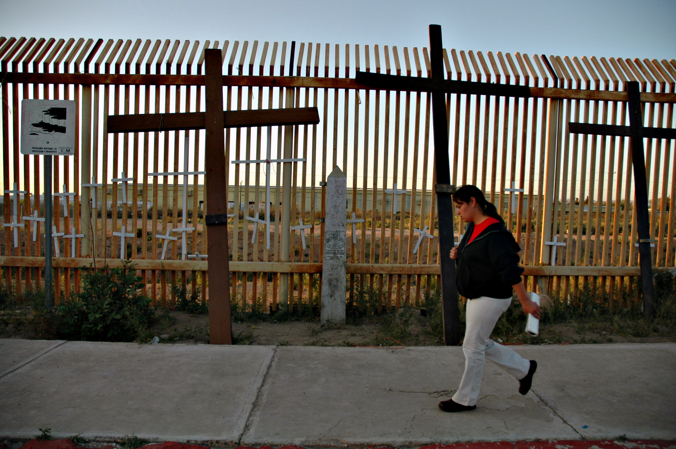 The border fence in Agua Prieta, Mexico, memorializes migrants who've died. Credit: Andy Isaacson