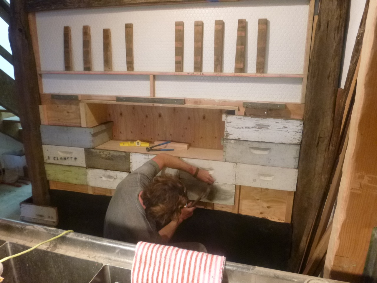 Hints of an Apiary: Nole installs bee hive box parts to the tap wall.