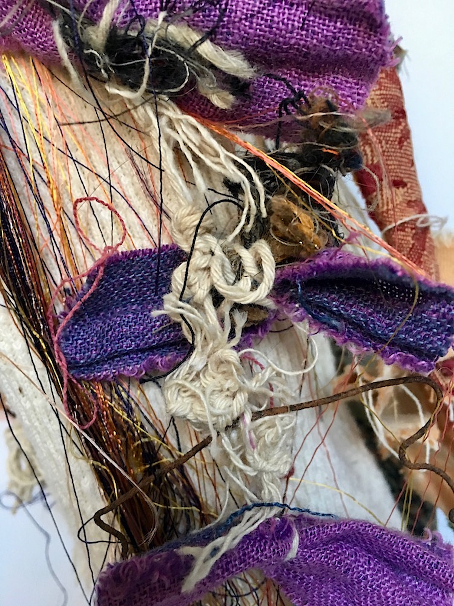"Mirror Eye (Detail)   Recycled textiles, mirrors, rust, elastic, string, paint, acrylic gel, thread, button, needle, nylon, rag rug, acrylic, beads, found felt, wool, stitched purple bow necklace, paper, and cement on industrial cardboard tube and base  32 x 7½"" round  2017"