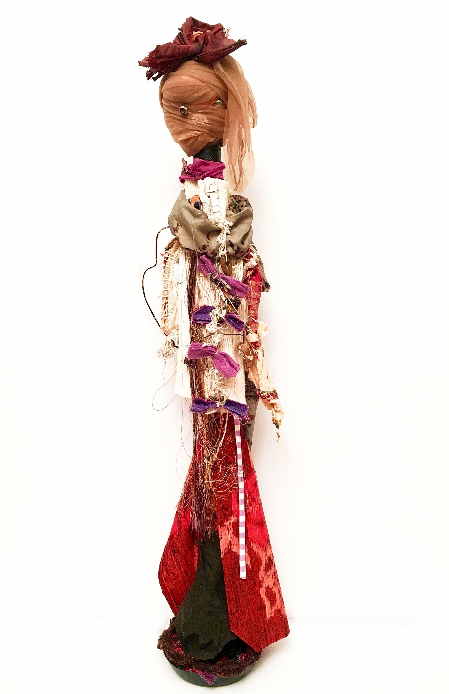 "Mirror Eye   Recycled textiles, mirrors, rust, elastic, string, paint, acrylic gel, thread, button, needle, nylon, rag rug, beads, found felt, wool, stitched purple bow necklace, paper, and cement on industrial cardboard tube and base  32 x 7½"" round  2017"