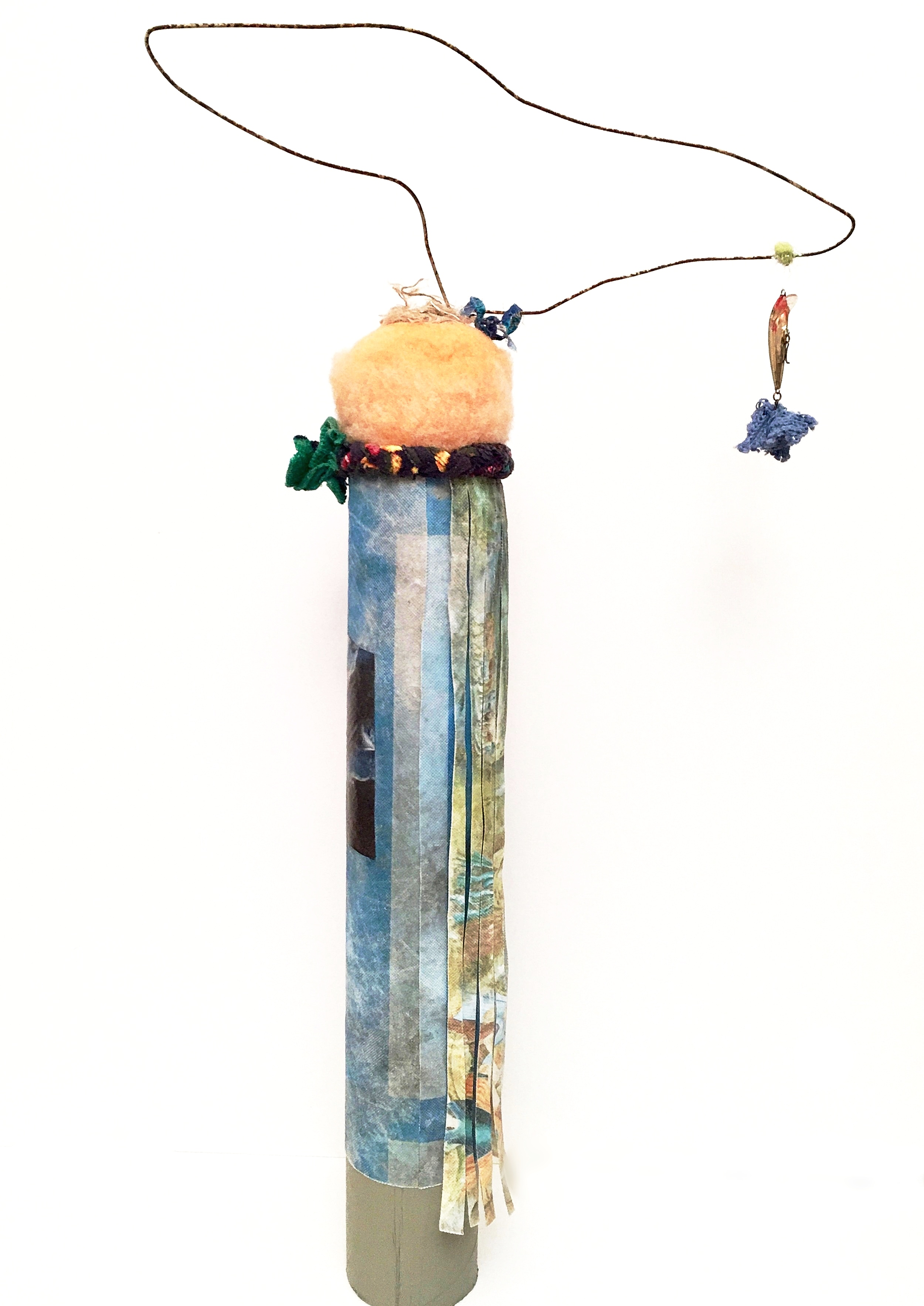 """Bluey with Lure   Basmati rice sack, woven textiles, sponge, fibers, rusty hanger, fishing lure, collaged paper, threads, paint, and acrylic gel on industrial cardboard tube  29 x 15½"""" round  2017"""