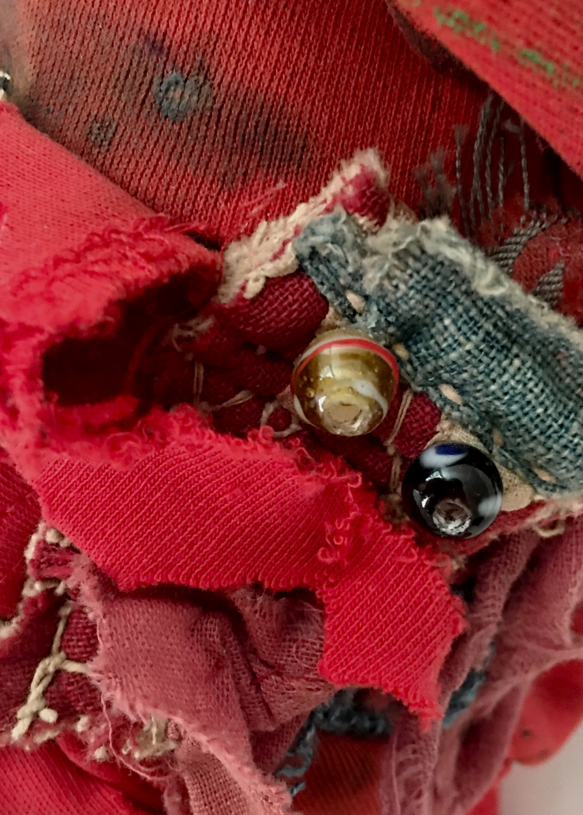 "Red Rag Shaker with Amulets (Detail)   Hand-painted red textile, antique Indian textile, buttons, threads, recycled textiles, and acrylic on industrial cardboard tube with hidden power amulets  14 x 8"" round  2015"