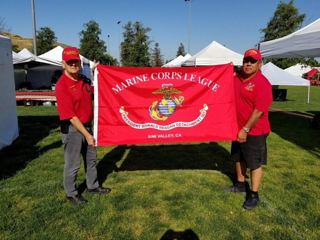 May 28, 2019   PDD Ben Pfister and John Fuentes exhibit the new Detachment 597 flag which will fly over the Veterans' Court in the Simi Town Center.
