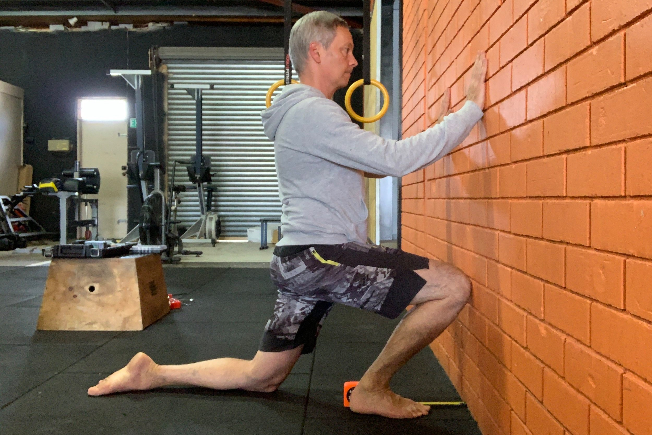 PASS: You can touch your knee to the wall without lifting your heel or letting your knee fall in