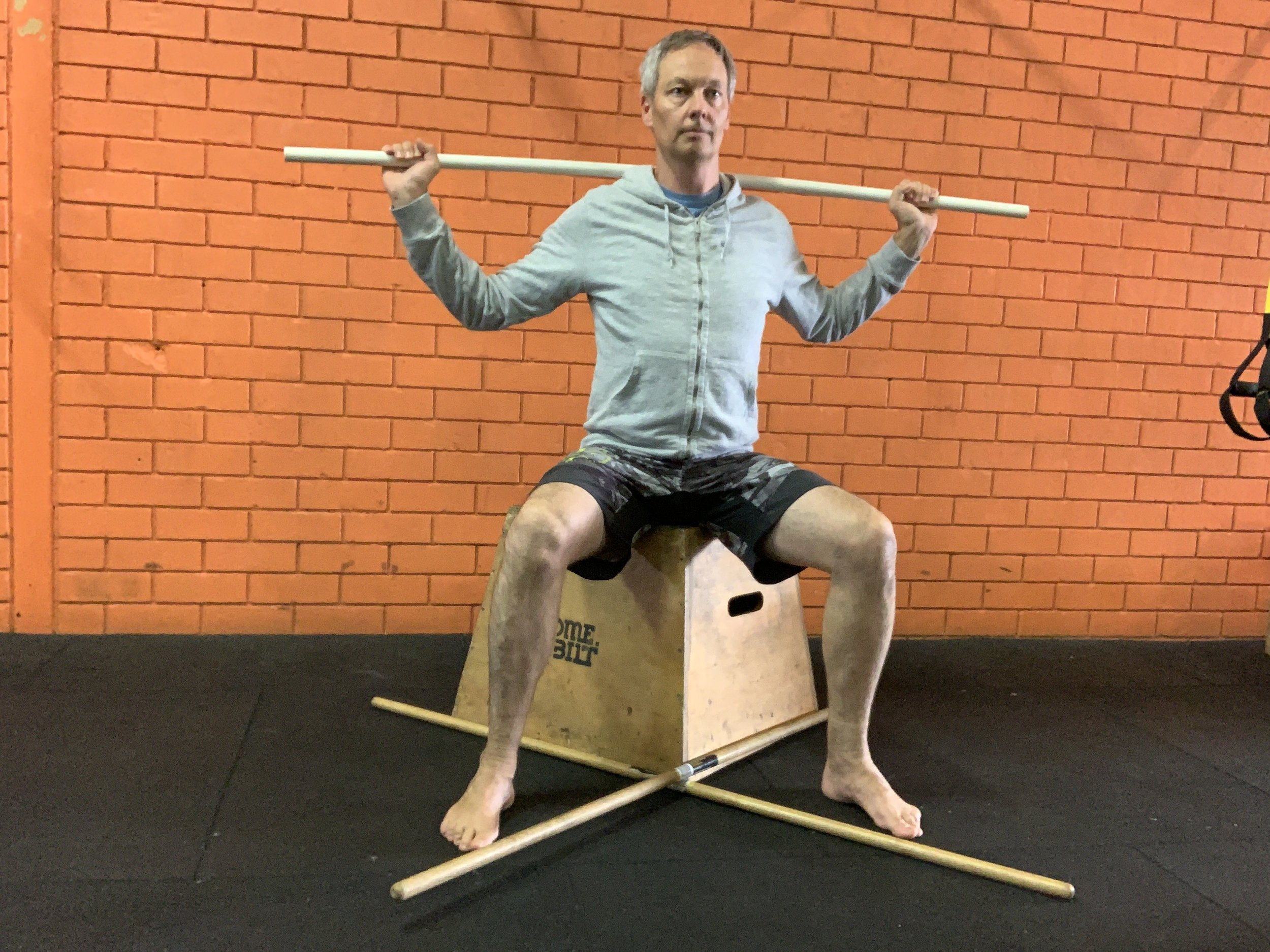 Sit on a box or bench, with two sticks at right angles at your feet, so that they point to the diagonals. This creates 45 degree lines from your midline.