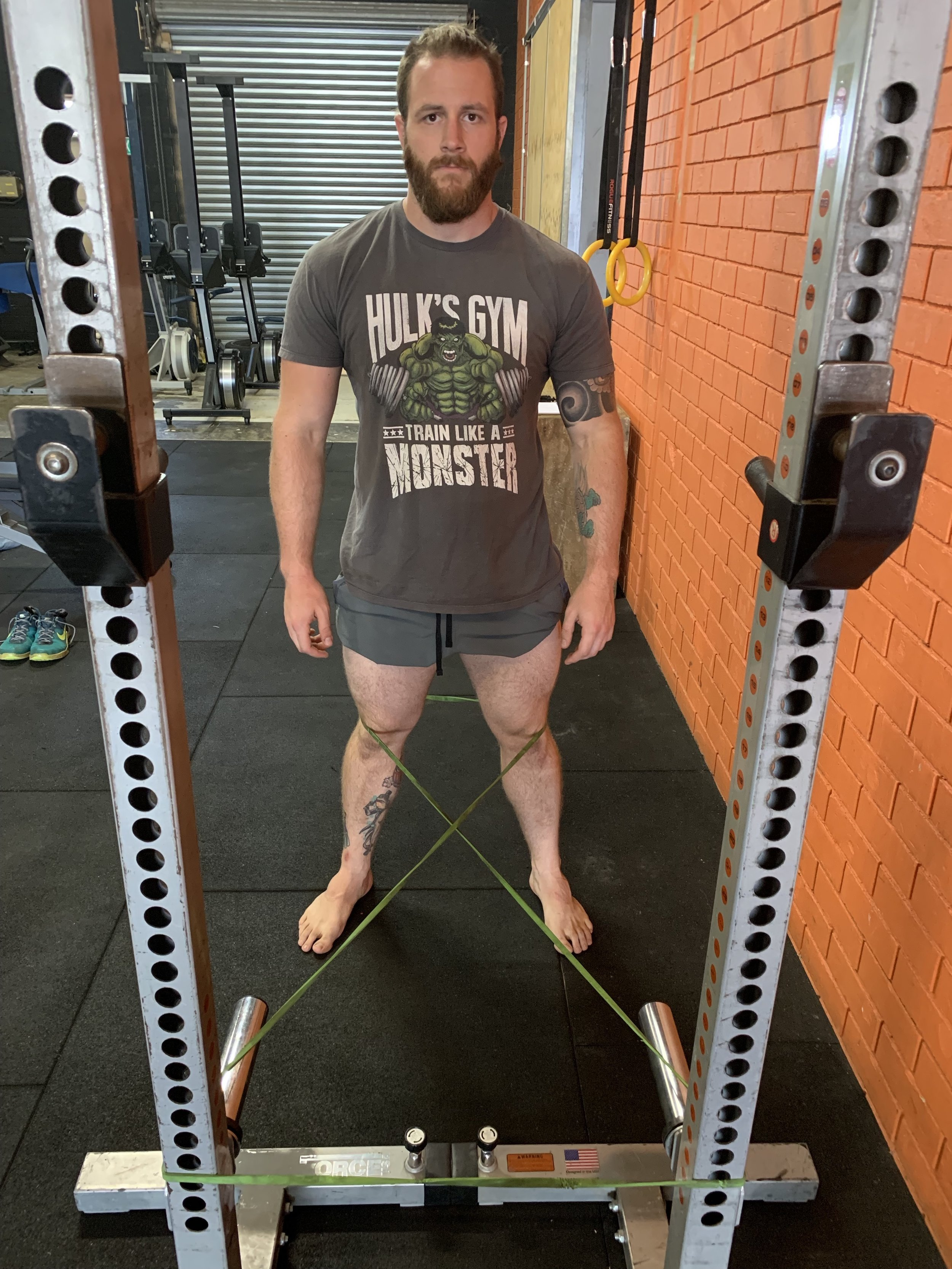 Set-up for using resistance bend to correct knee valgus while squatting.