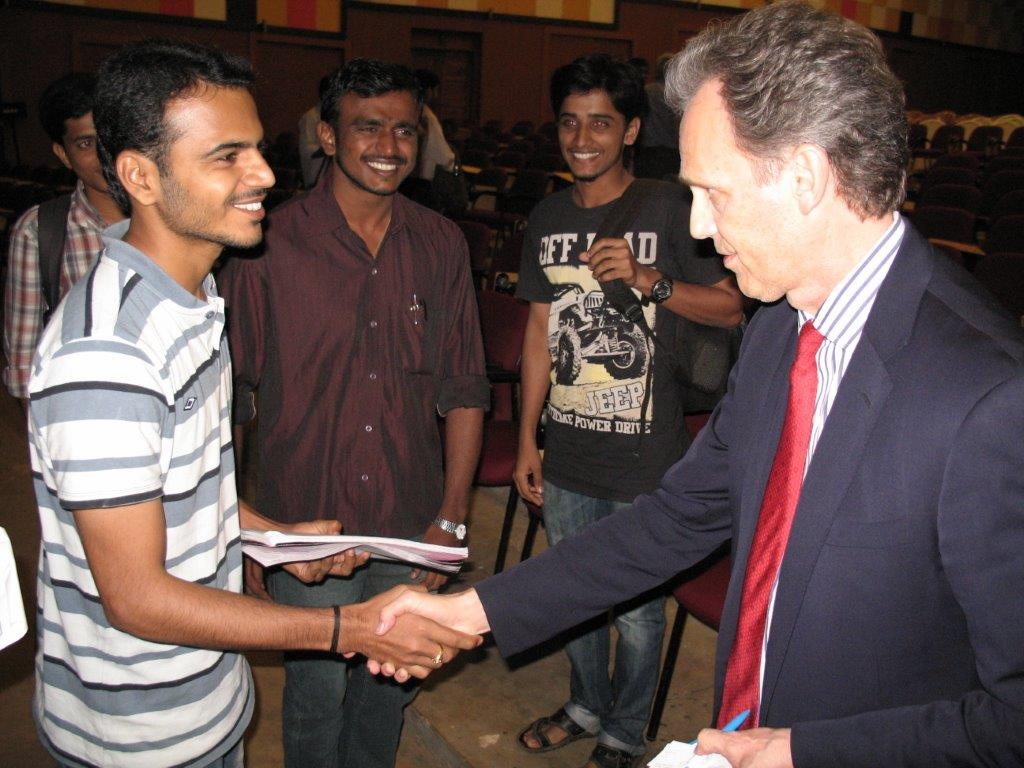 David Wiebers, M.D., shakes hands with student during   Q&A session after the Theory of Reality presentation   at Mangalore University.