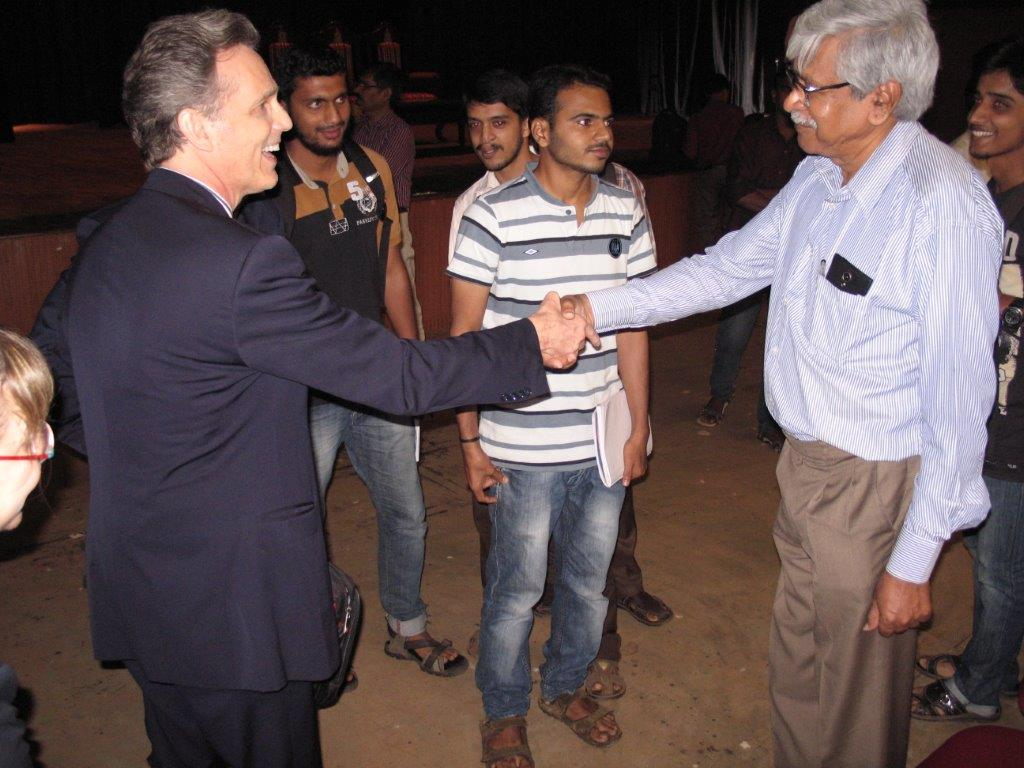 David Wiebers, M.D., shaking hands with physics professor at Mangalore University.