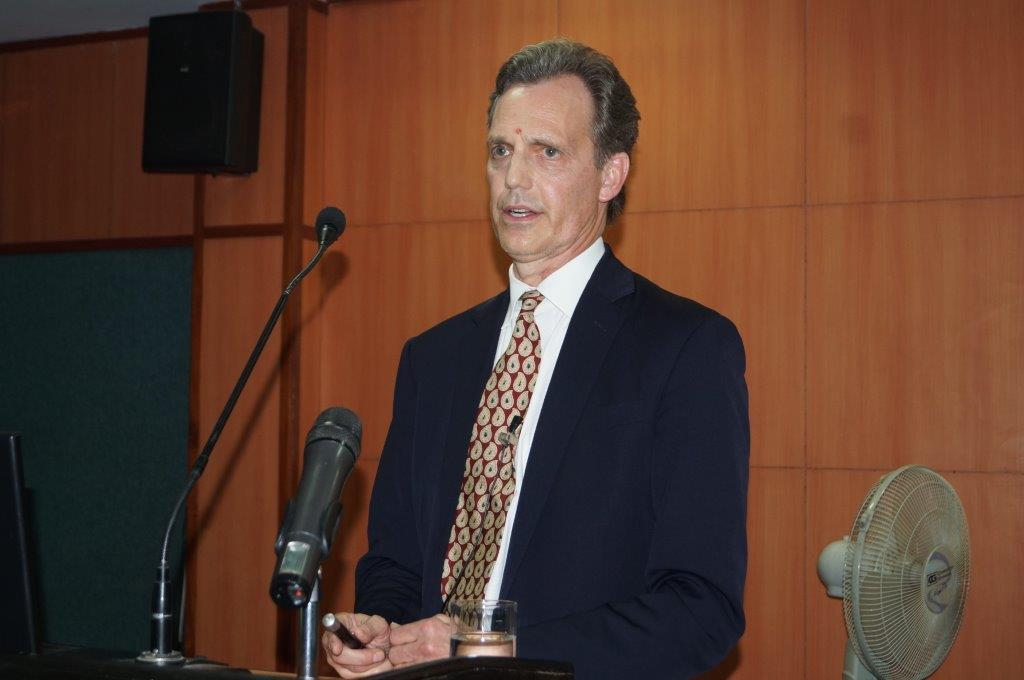 David Wiebers, M.D., at the podium at Amity University Delhi campus delivering Theory of Reality presentation on November 9, 2015.