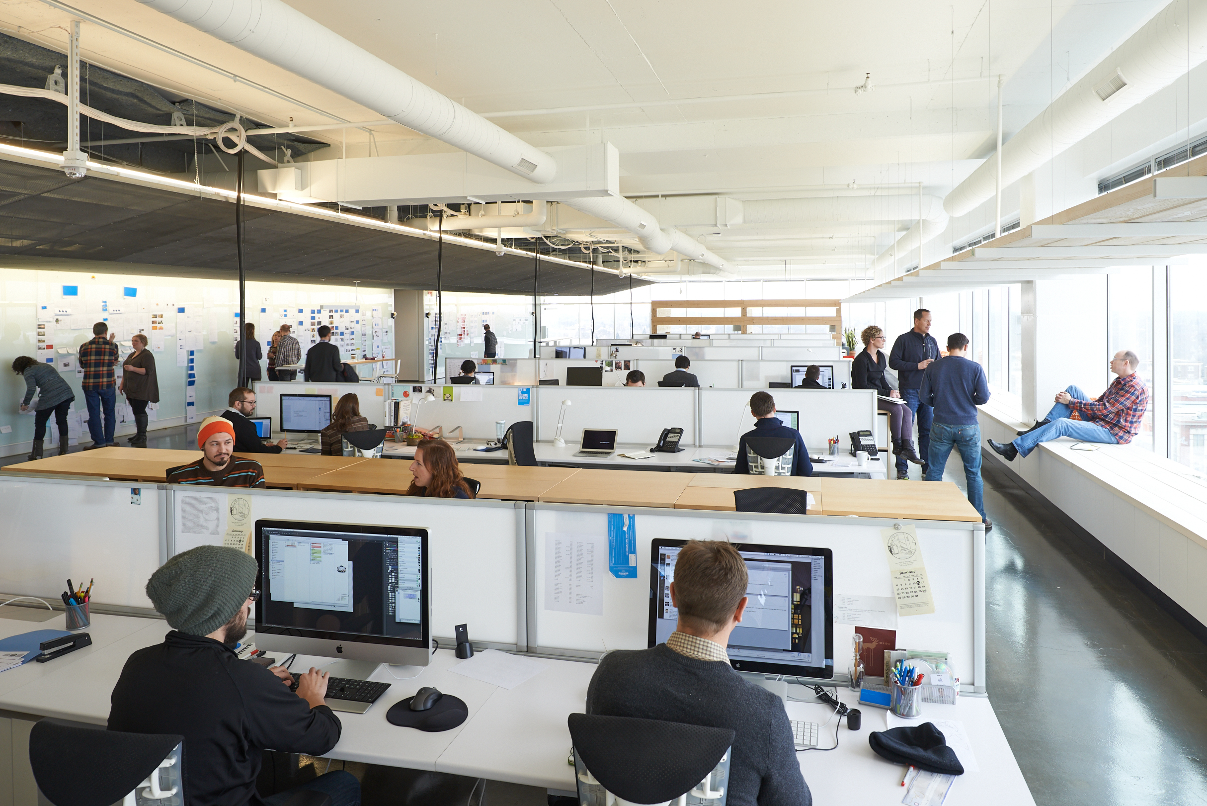 An idea wall for collaborative brainstorming runs parallel to rows of individual work tables, keeping employees connected.