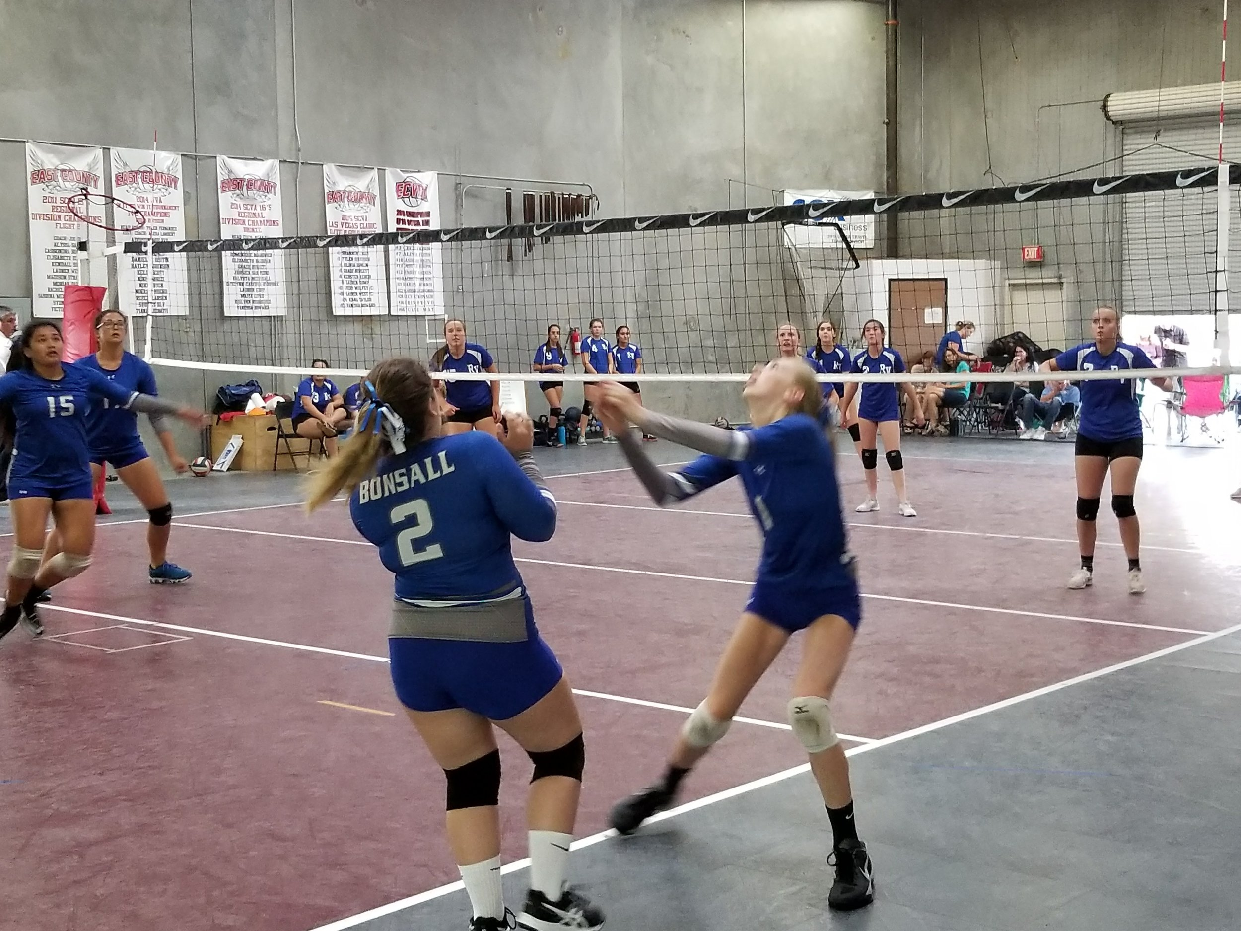Abigail Reinard #1, stretches for a difficult setter-hit toward MaiCai Meluat #15 and Ashlin Smith (far left of court) in game 2, the first BHS win. Team Captain Alexandra Beker #2, calls the shots.