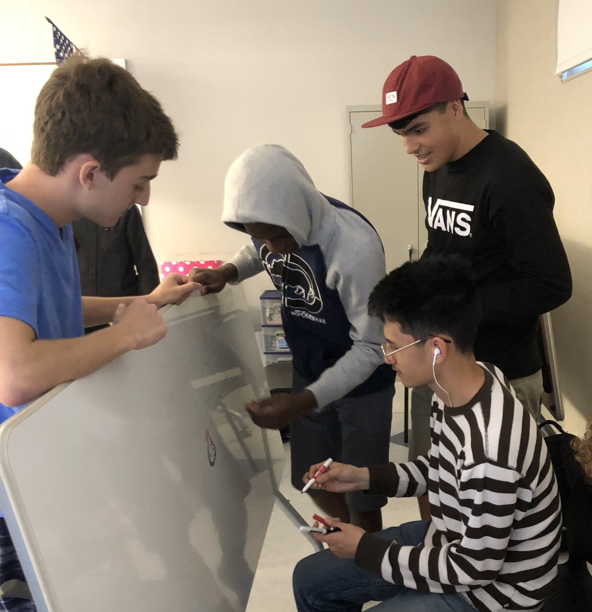 Students in a group writing on white board