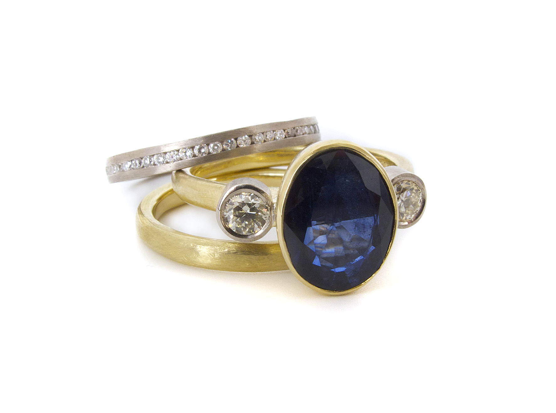 This remake of an engagement ring with the customer's own oval sapphire and diamonds into a beautiful new trilogy engagement ring completed with wedding band and diamond eternity band. All 18ct white & yellow gold, with a soft organic textured look to the bands.
