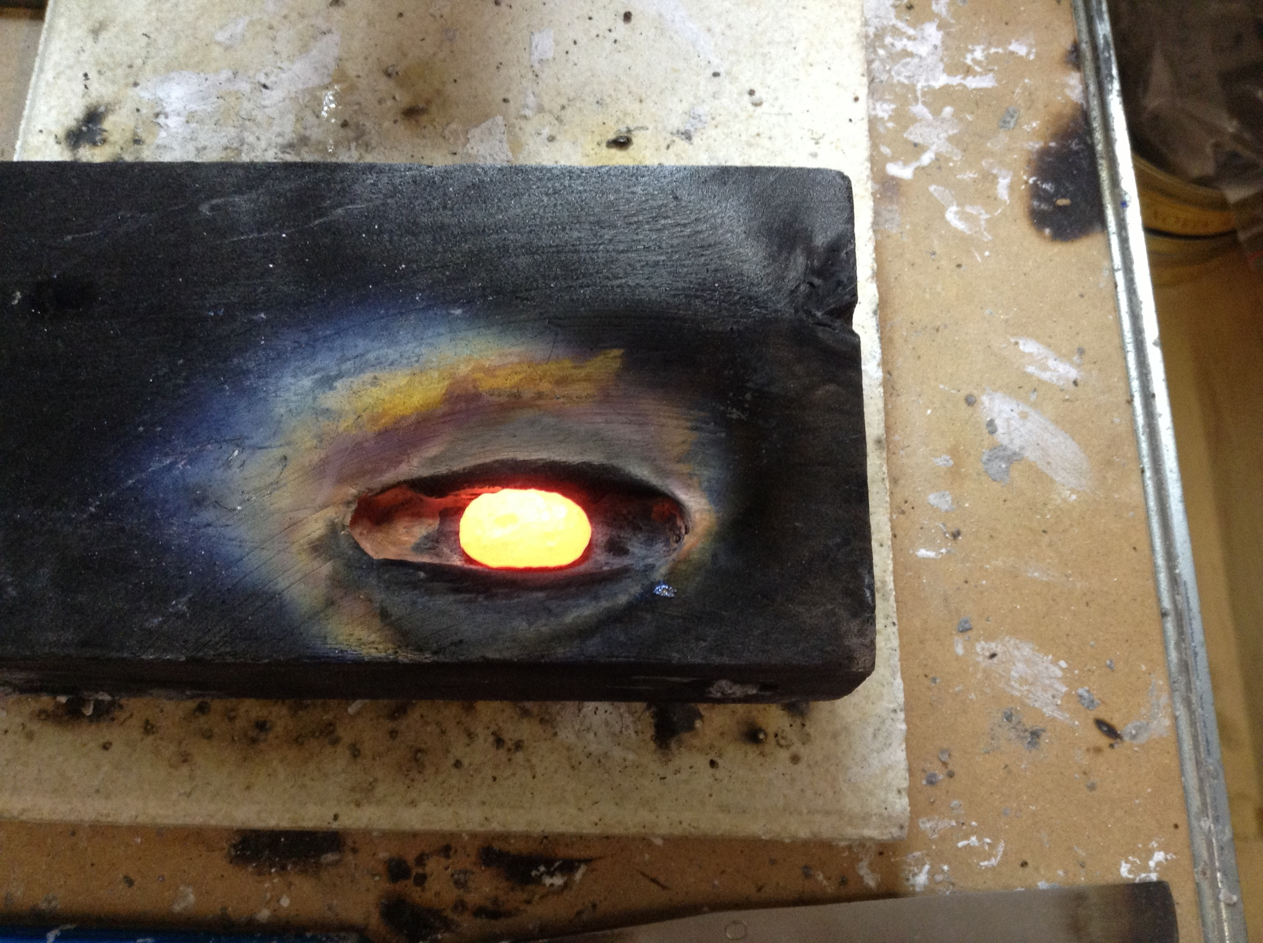 Glowing hot ingot, fresh metal to use made from scrap and offcuts.  Melted into a charcoal block.