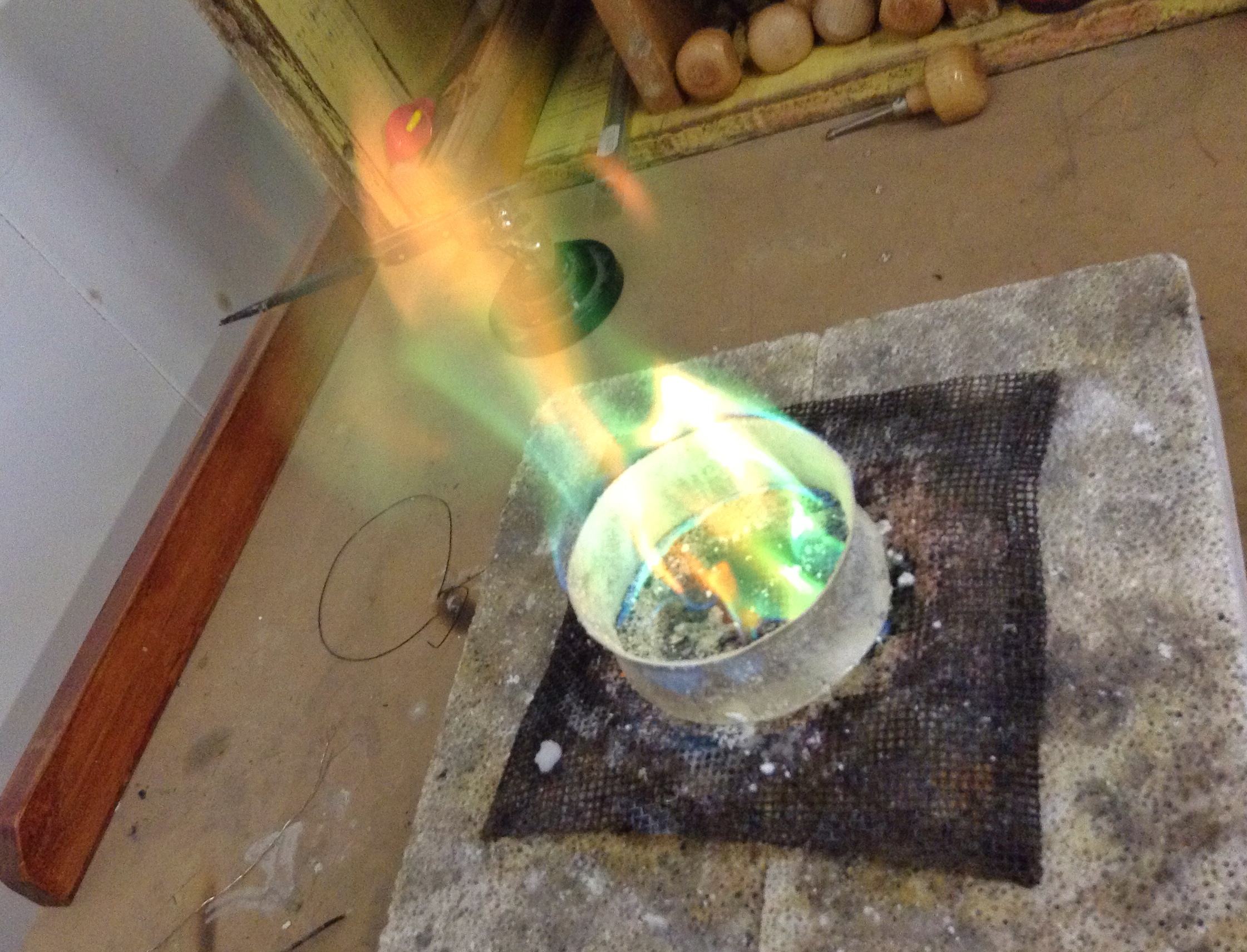 Burning off a resist powder applied to the metal before annealing (softening to forge).  The powder helps with resisting a stain on silver known as firescale.