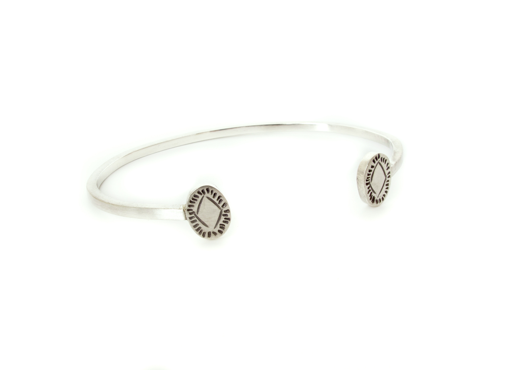 this wrist cuff has some subtle detail on each end, oval shaped with fine hand stamped details, in sterling silver.