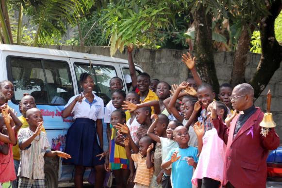 The Rev. Robert N. Sieh, director of The United Methodist Church's Bishop Judith Craig Children's Village, and children pose with their new bus.  Photo by E Julu Swen, UMNS..jpeg