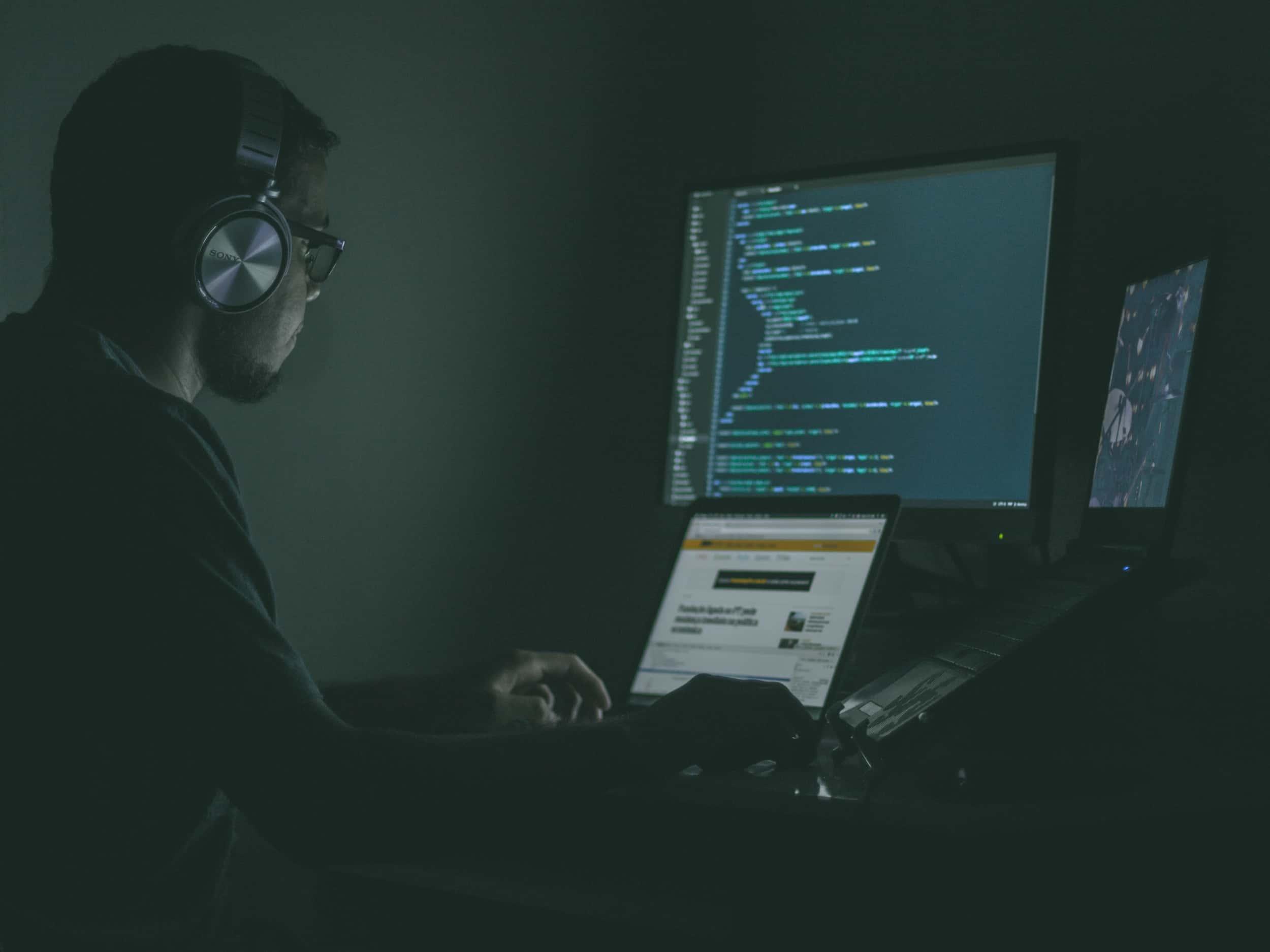 Hacker vor mehreren Computermonitoren im Dunkeln