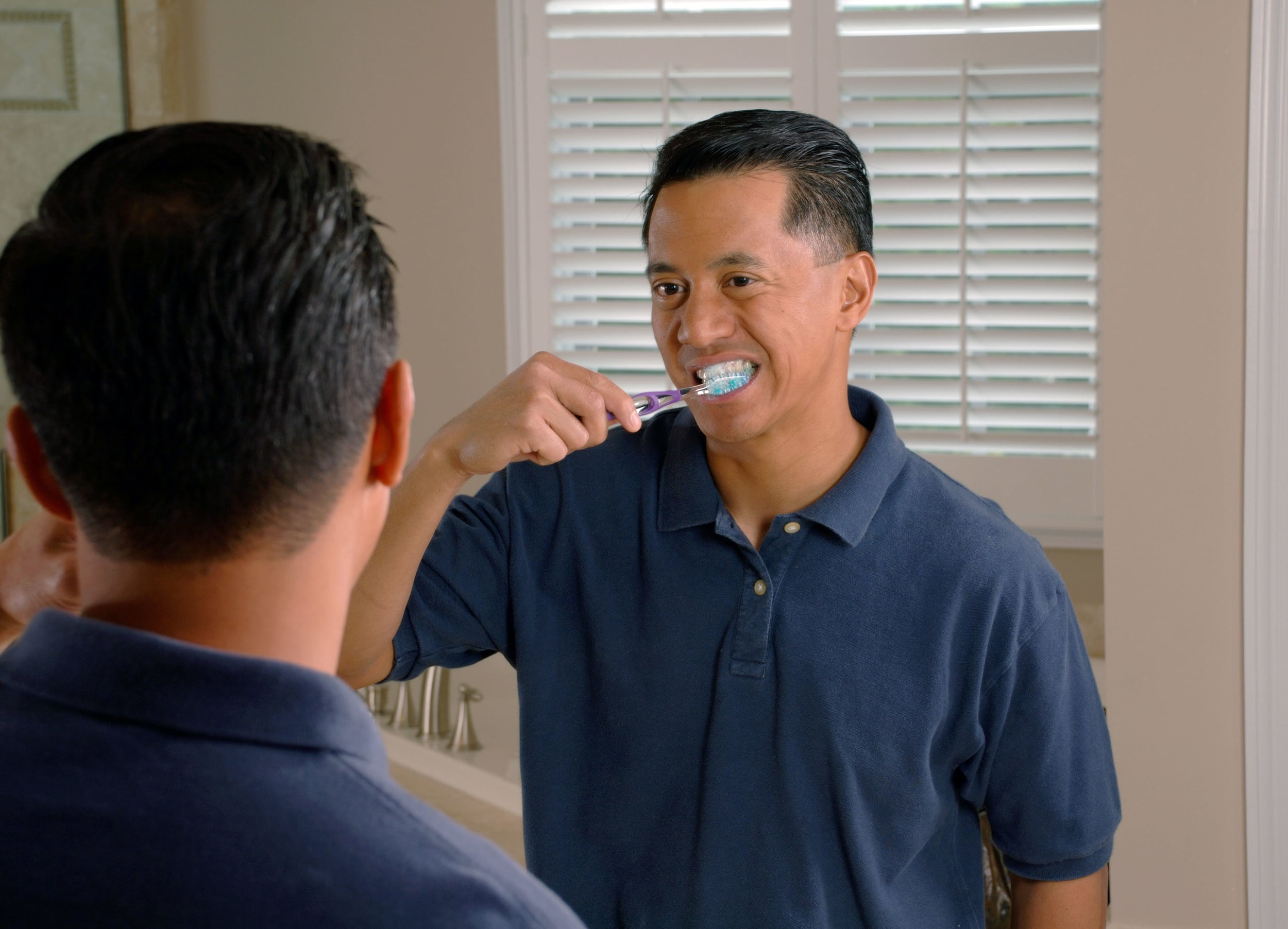 This is a man brushing his teeth!
