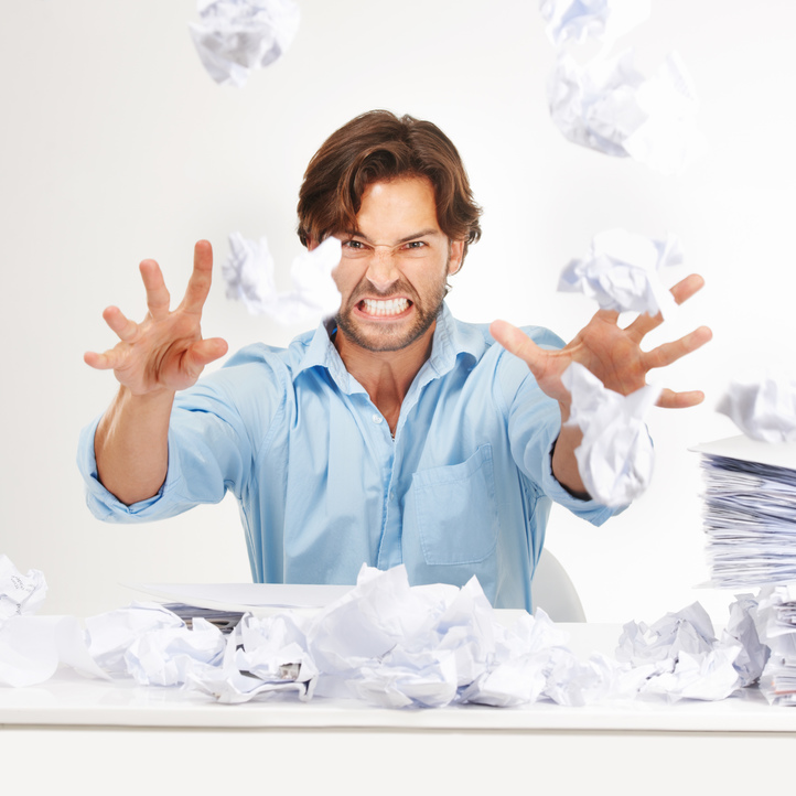 Frustrated man in blue shirt gritting his teeth throwing paper at screen