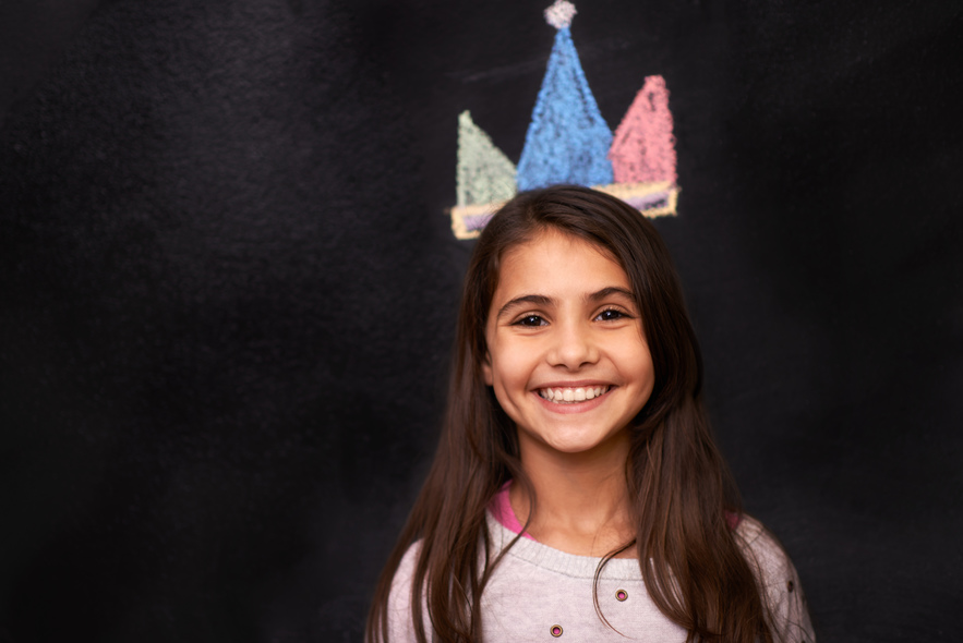 Child with crown on chalkboard