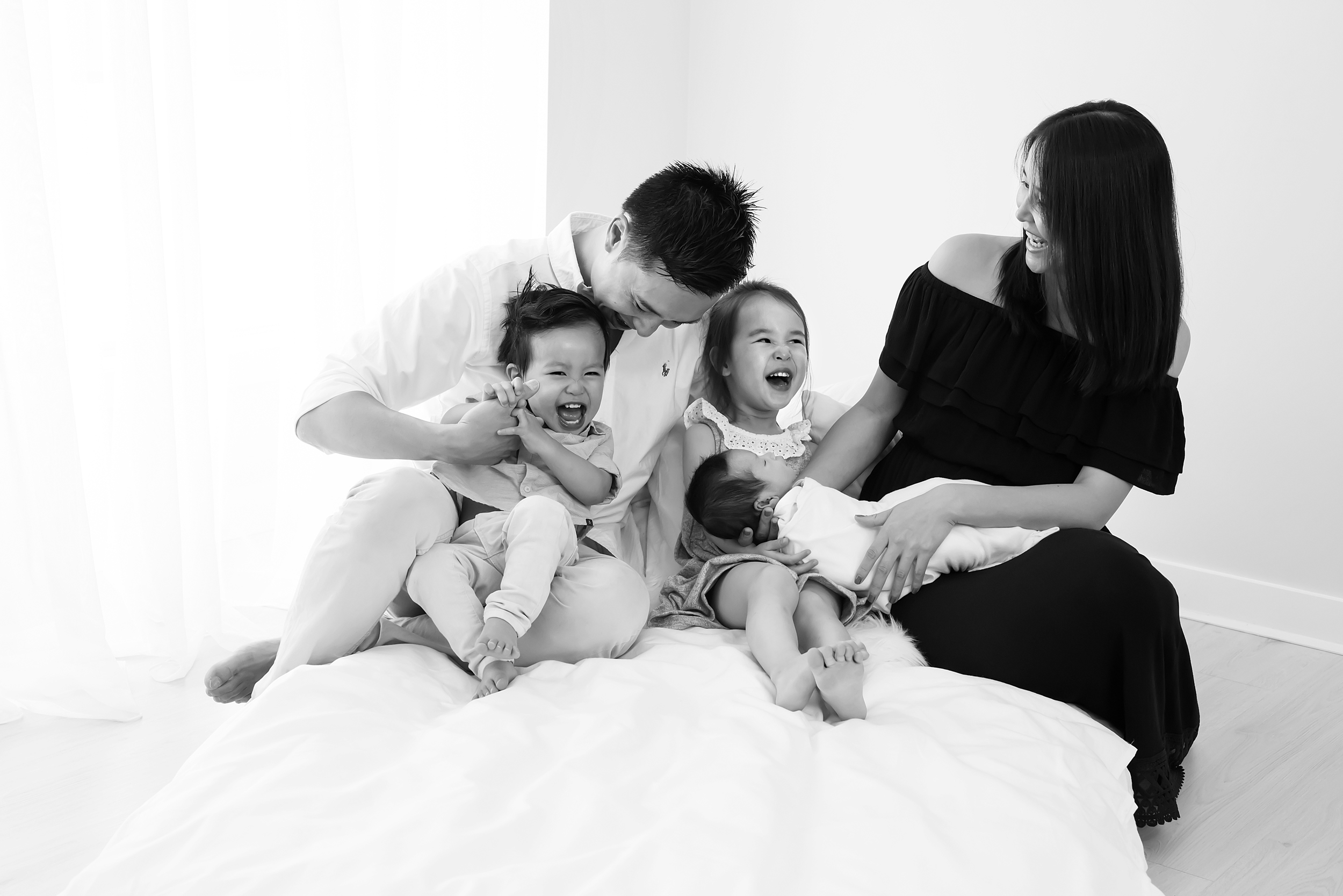 A candid photo of a Melbourne family with their newborn baby taken by Melbourne newborn photographer, Monique Graham