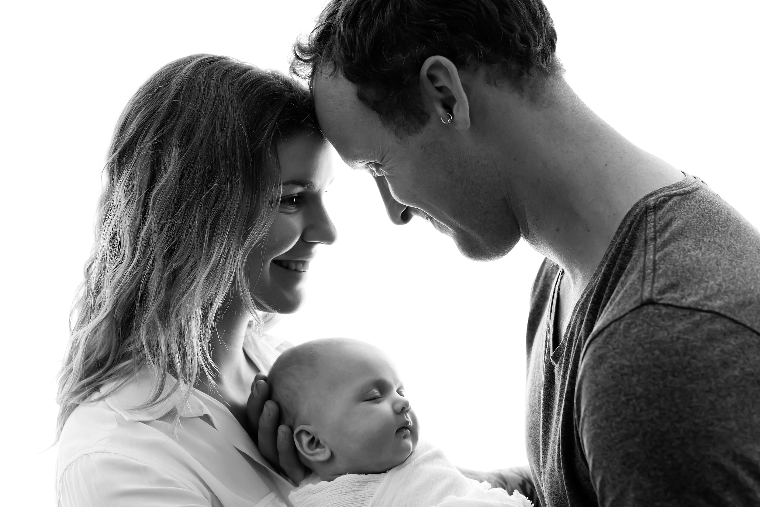 Photo of a Melbourne couple holding their newborn baby girl during a professional photo session.