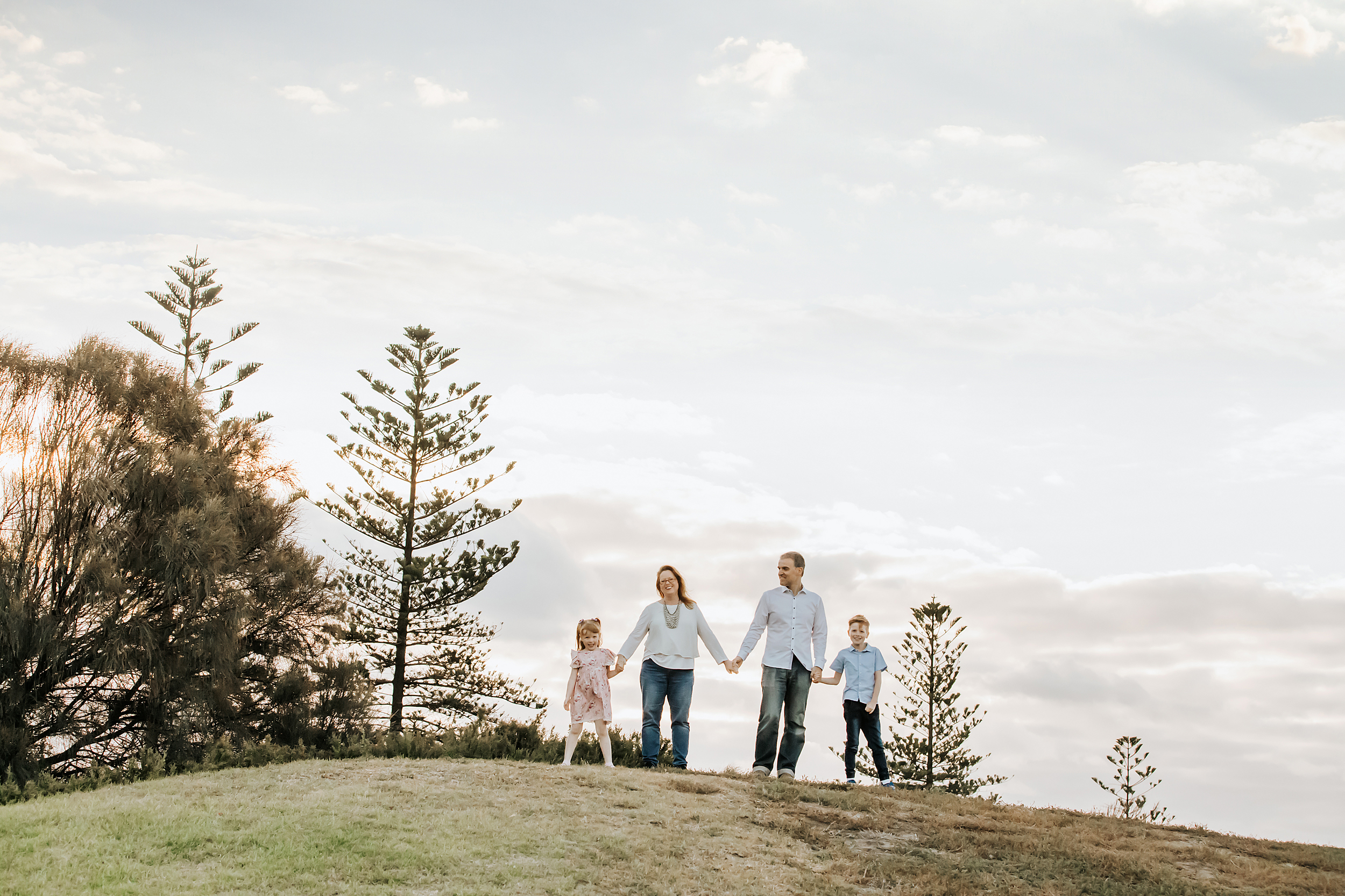 A family photo featuring a family of four standing on top of a hill all holding hands.  Taken by a professional photographer in Melbourne