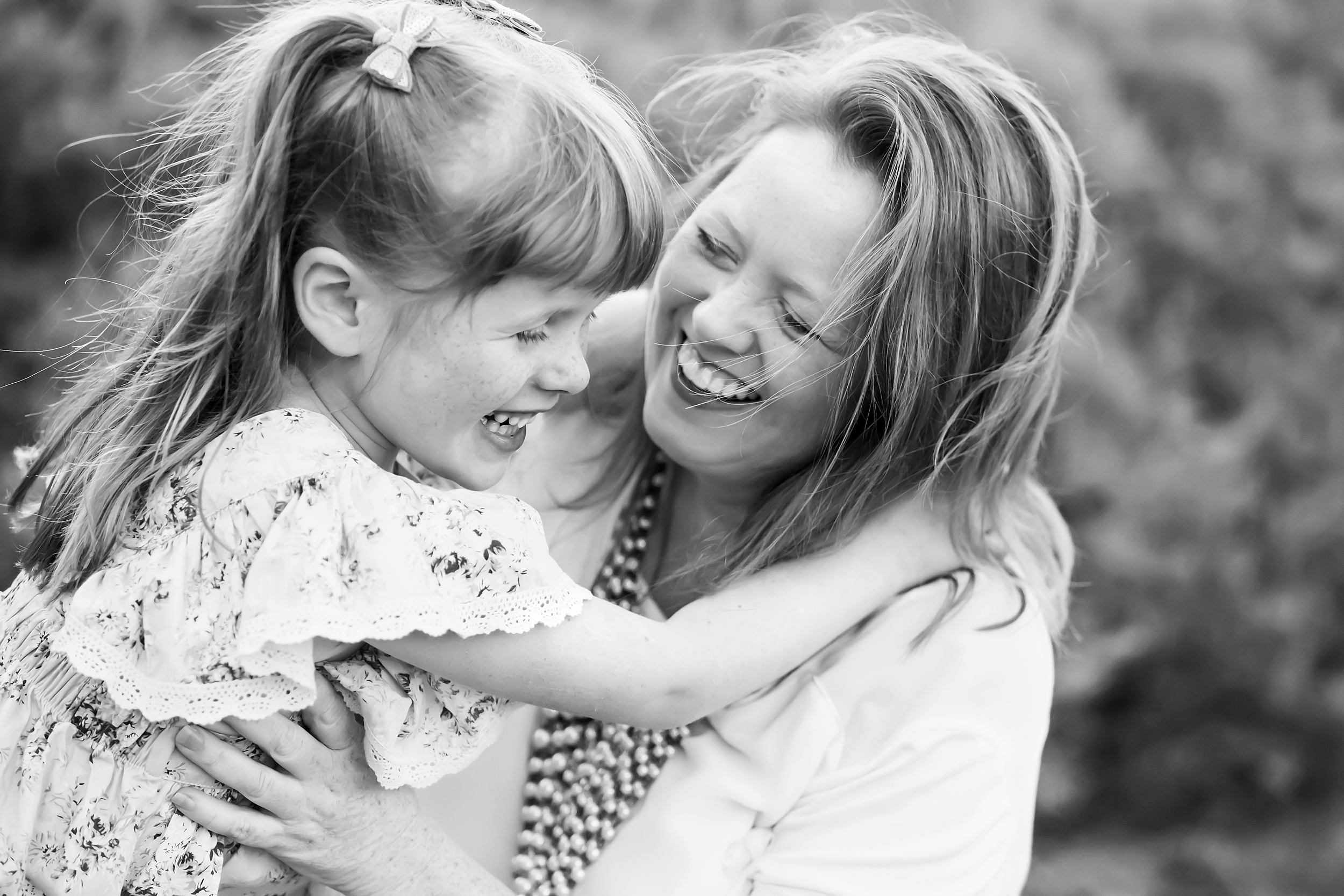 A black and white photo of a mother and daughter laughing together taken by a family photographer in Melbourne