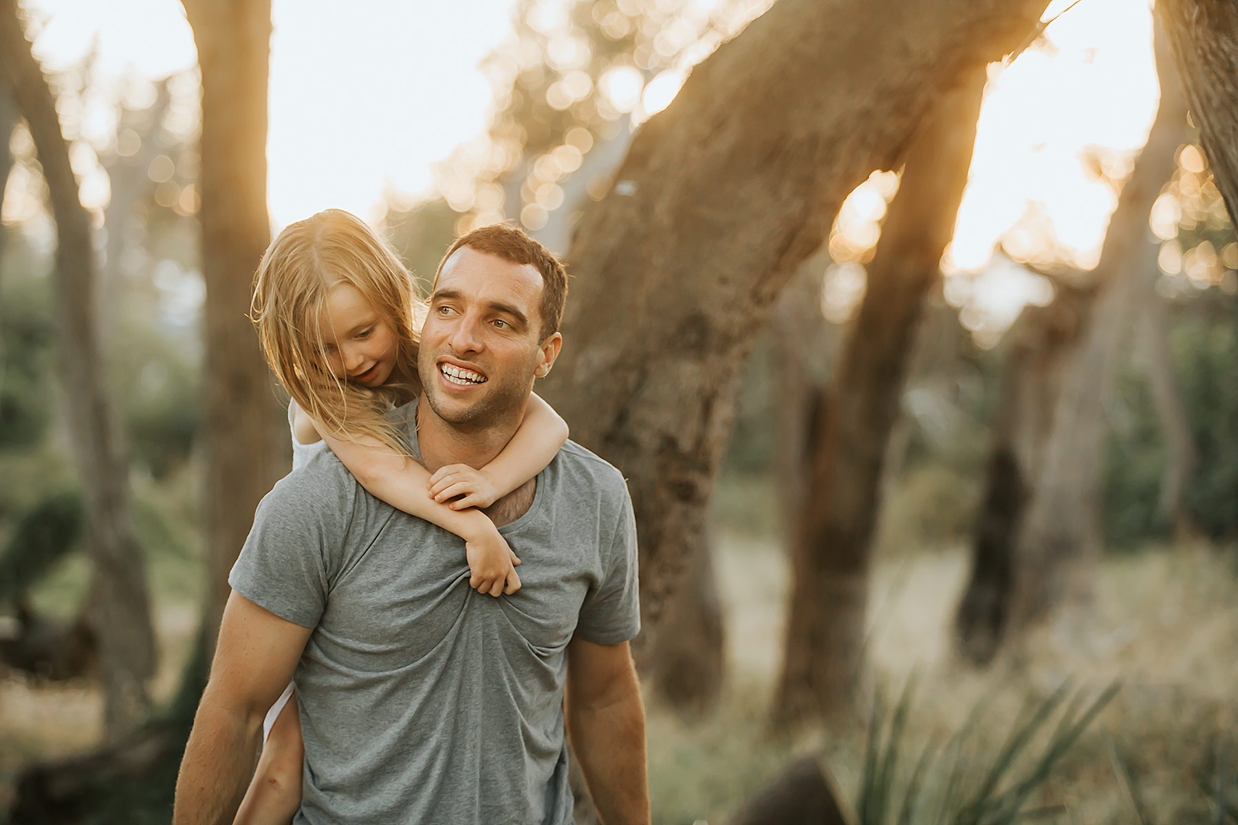 Taken during golden hour on the Mornington peninsula, a girl having a piggy back on dad's back during family photo session.