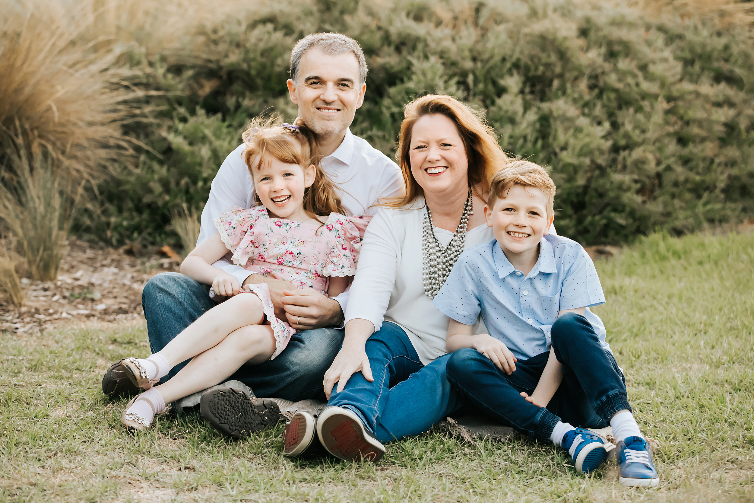 A natural family portrait of a family of four sitting on the grass during golden hour.  Taken by a Melbourne Family Photographer.