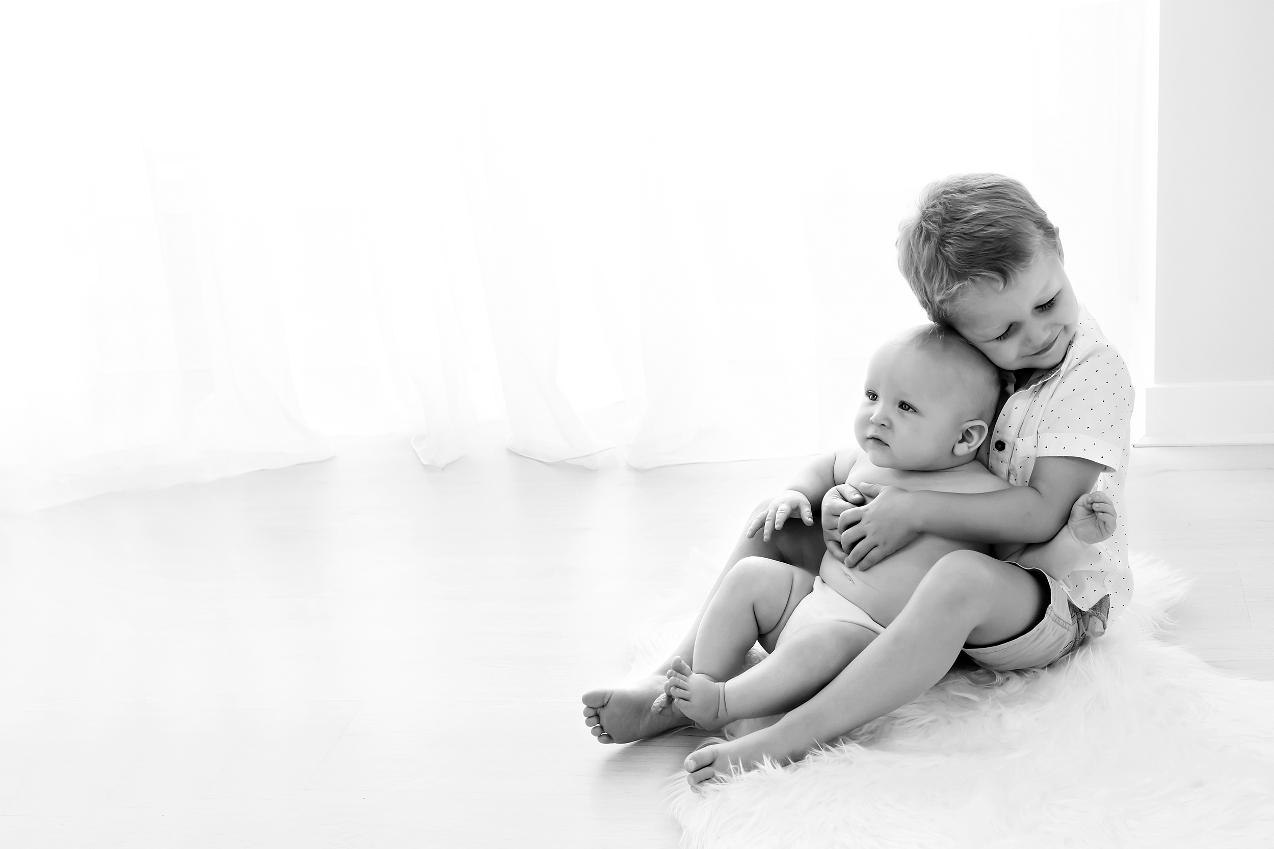 Black and white photo of older brother cuddling younger brother taken during baby photo session in Melbourne