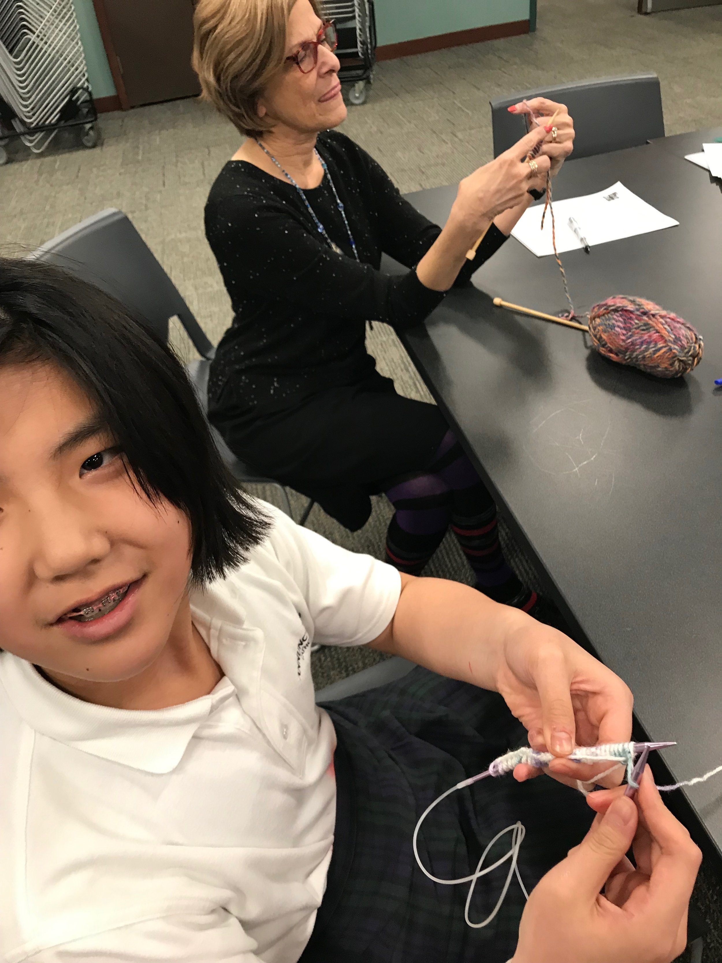 Librarian Ginger and LitKnitter Izzy knitting together at the first LitKnit circle session this week at Washburn Library in South Minneapolis.