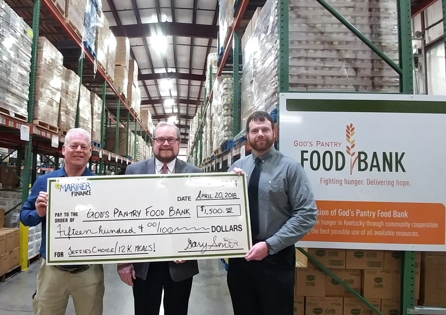 Mariner Finance representatives Gary Smith and Joe Keys are thanked by God's Pantry Food Bank CEO Michael J. Halligan for their generous gift to feed hungry neighbors in Central and Eastern Kentucky.