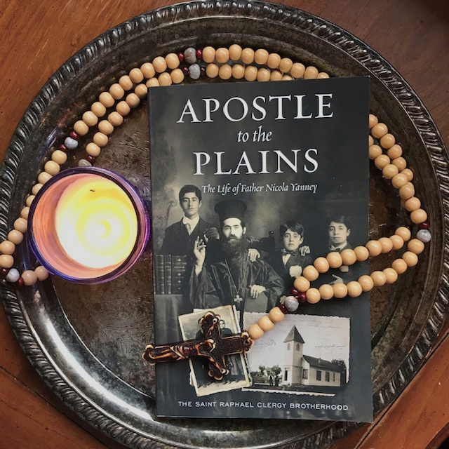A photo of the book cover of APOSTLE TO THE PLAINS with a prayer rope and lit candle.