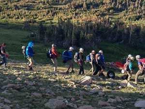 Rescuers performing wheeled trail carry evacuation of an injured hiker below St. Vrain Mountain, Indian Peaks Wilderness Area, August 7, 2014