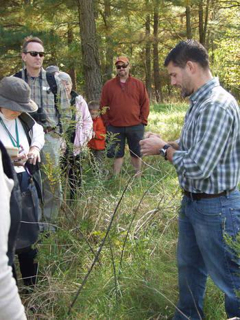 Dr. Schindler identifying a plant at Adkins Arboretum