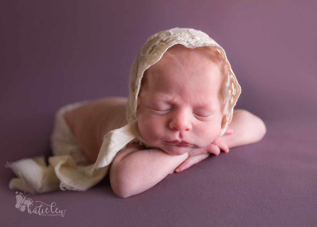 A baby girl twin wearing a lace bonnet