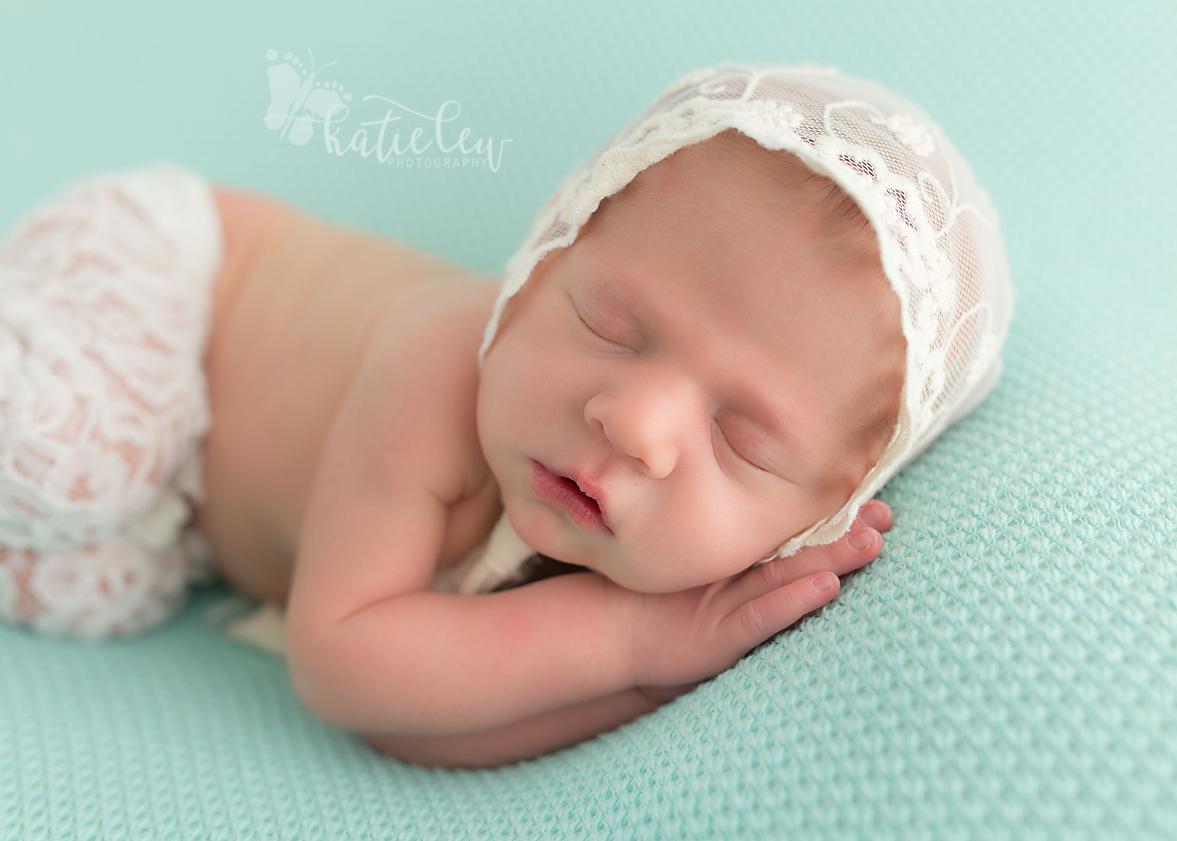 newborn baby girl wearing lace pants and a lace bonnet on a blue blanket