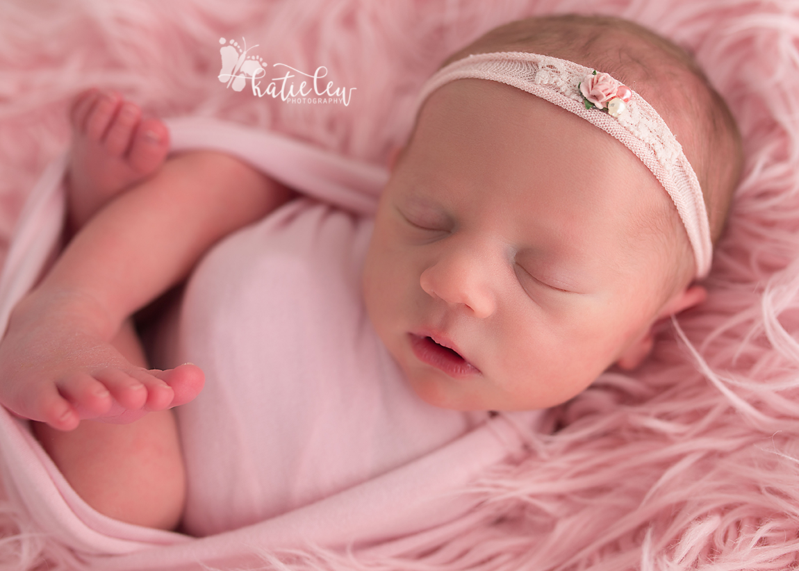 Newborn joy ann nestled in pink fur and wrapped up