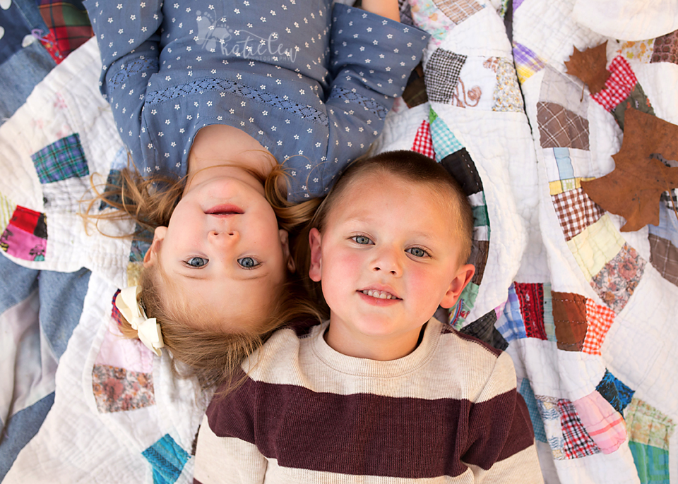 Joy Ann's older brother and sister laying on a quilt during their fall family session