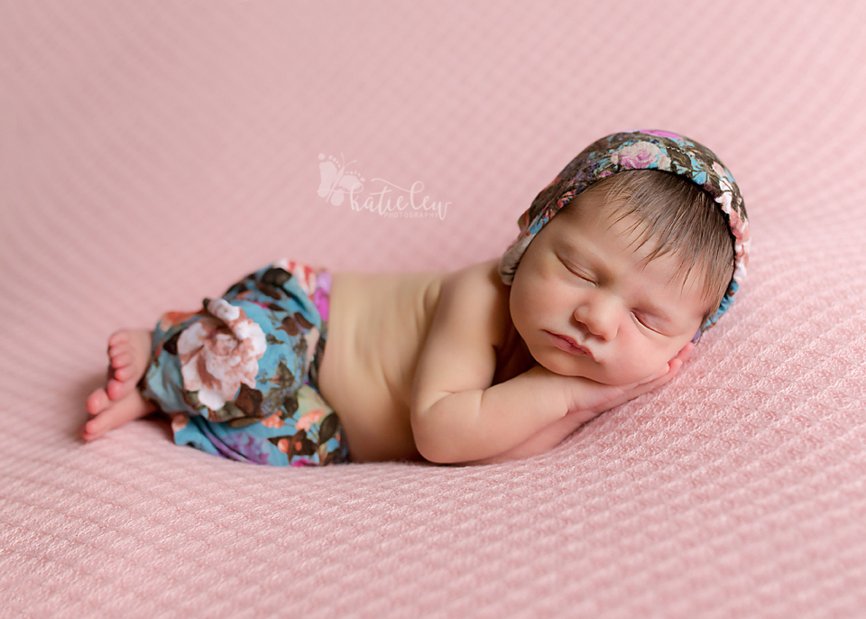 A baby girl wearing a blue floral outfit sleeping on a pink blanket