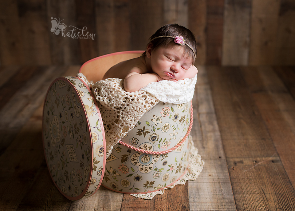 Newborn girl resting peacefully in an antique hat box