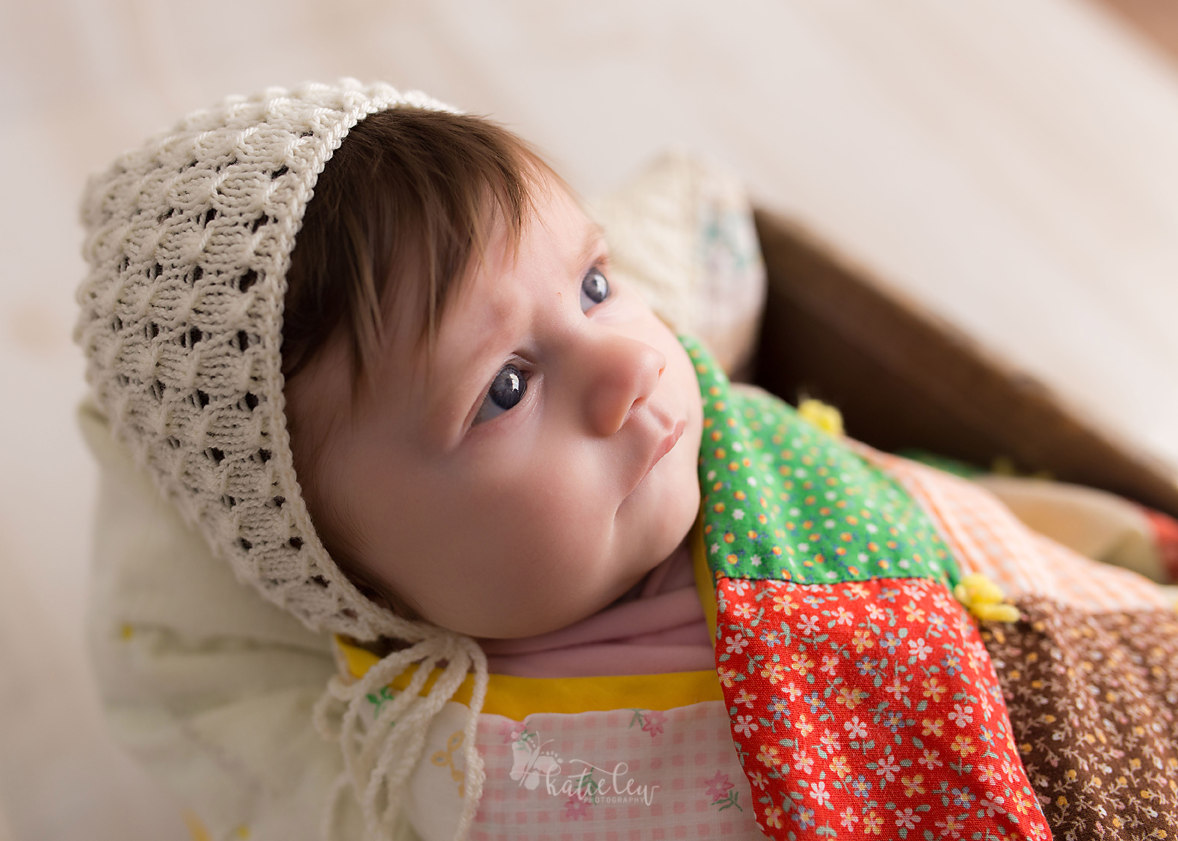 little baby wearing a bonnet and wrapped in a quilt.