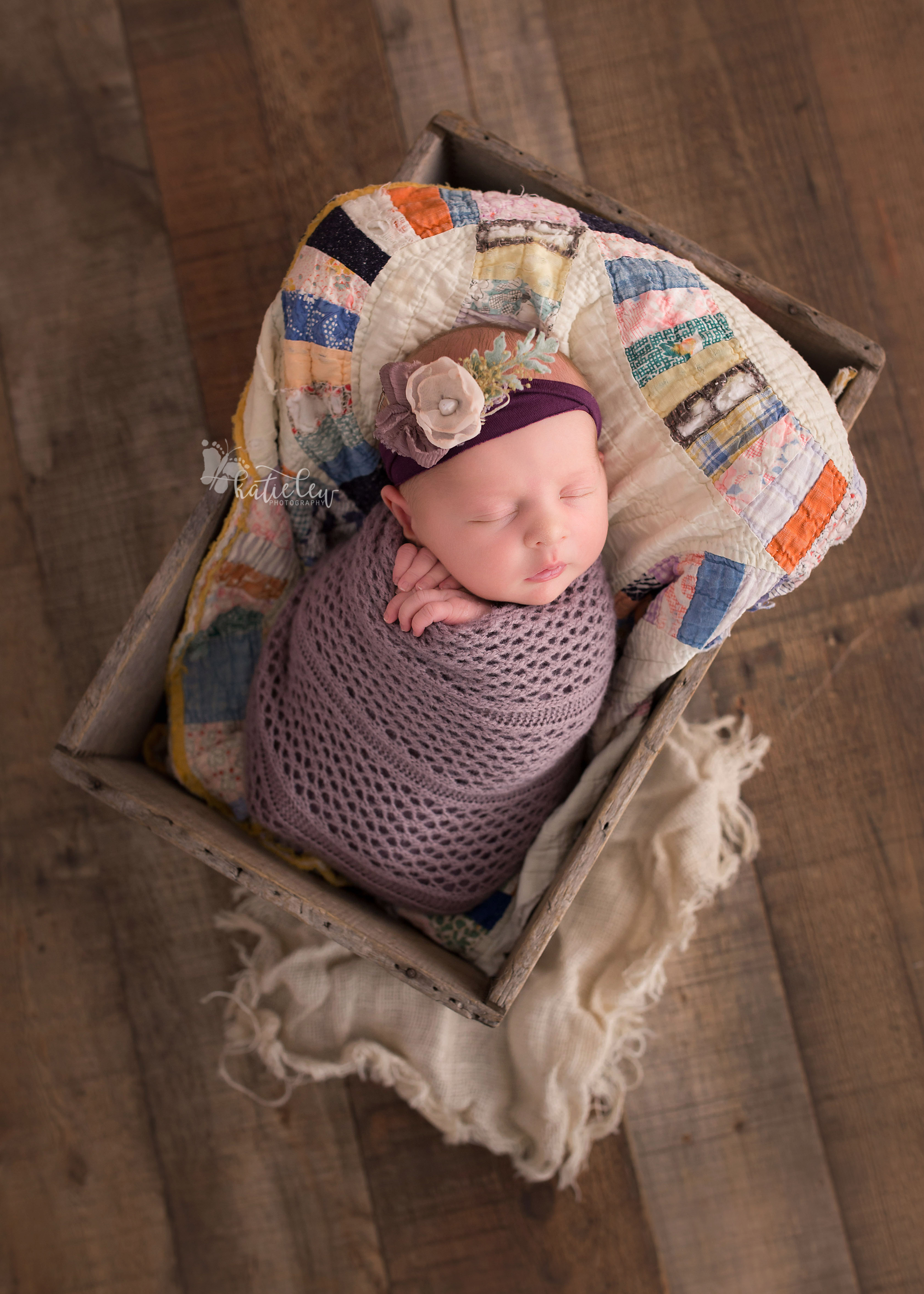 Tulsa newborn wrapped in purple and nestled in an old crate