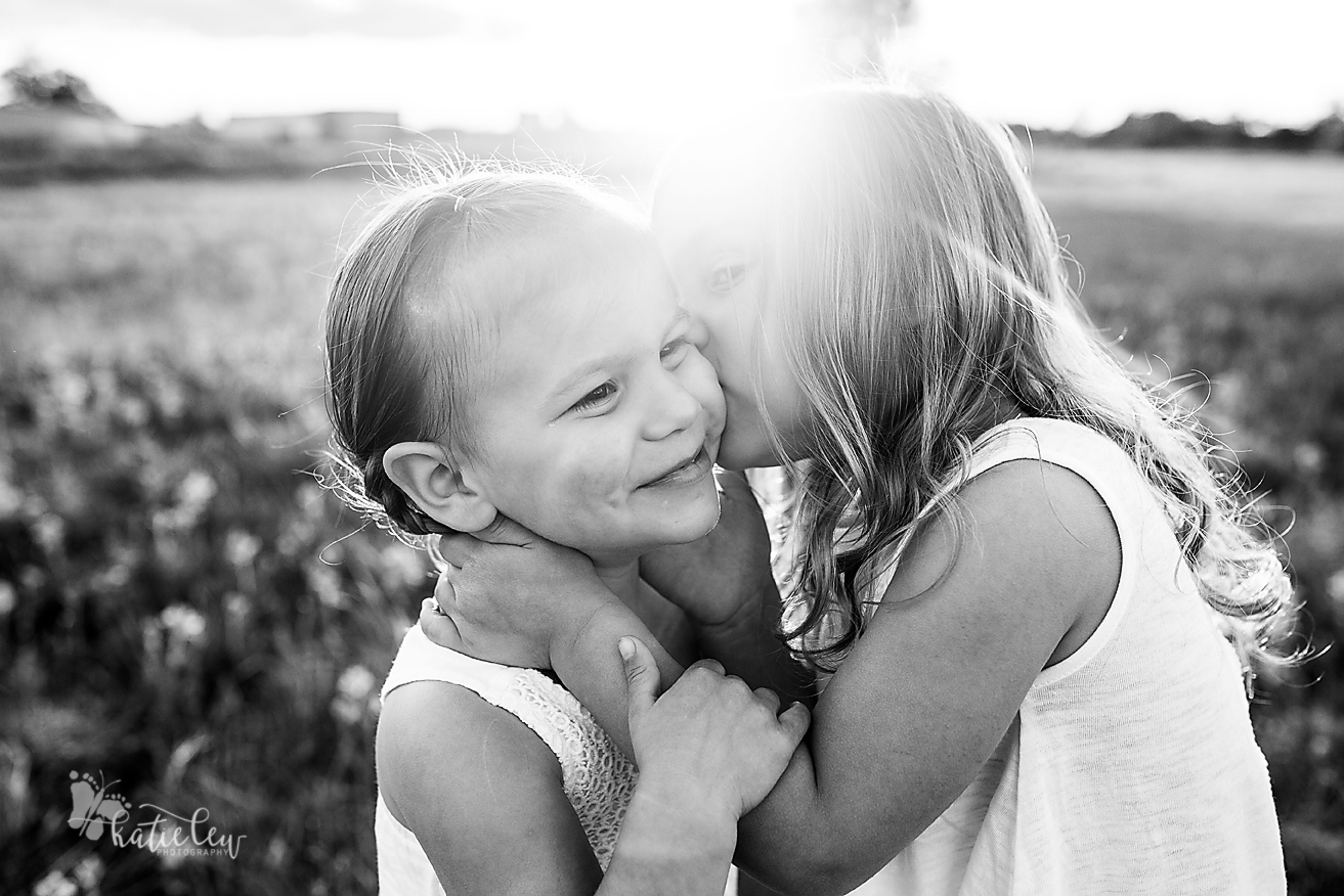 Older sister giving baby sister a kiss on the cheek.