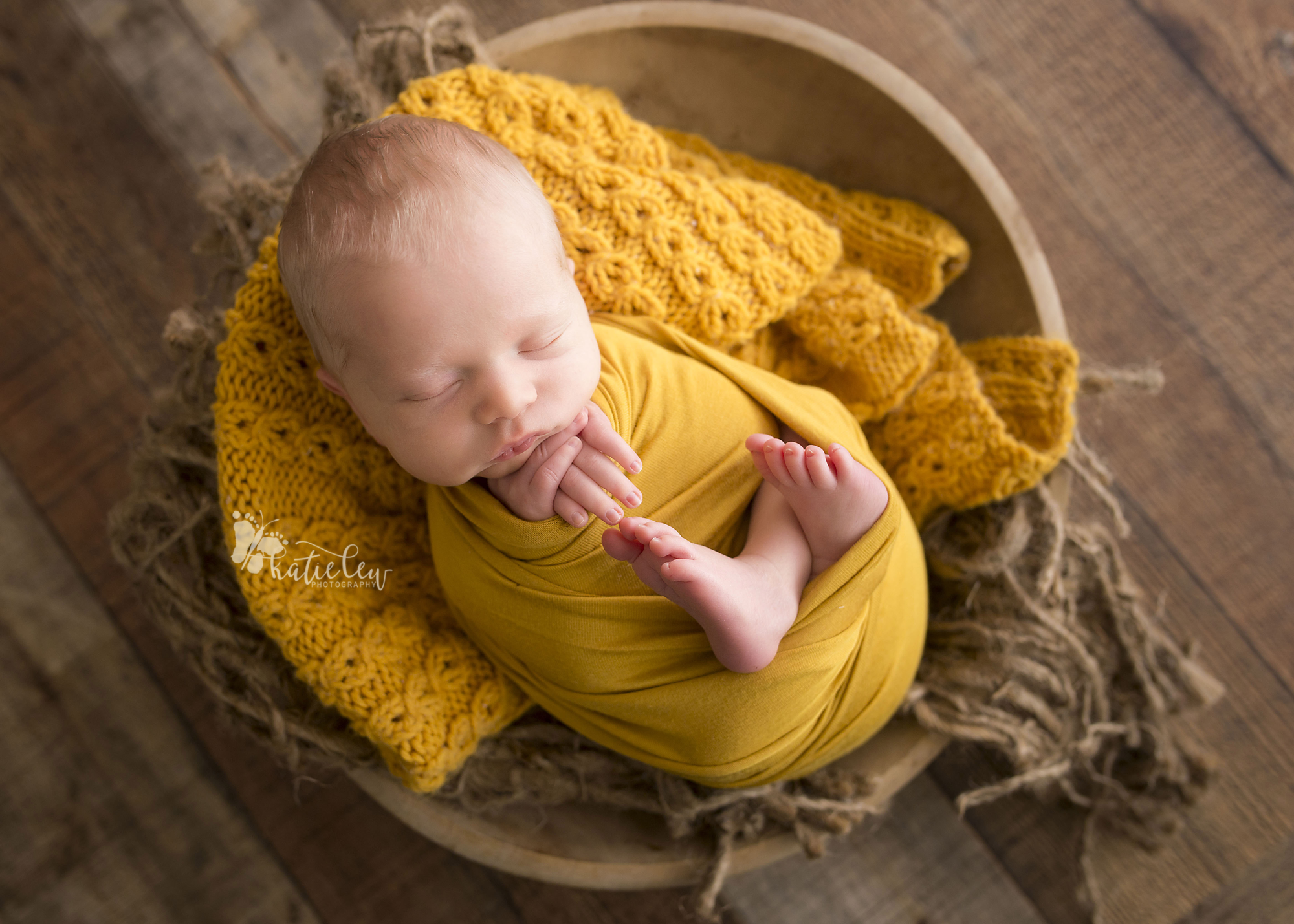 newborn boy wrapped in mustard and nestled in a bowl